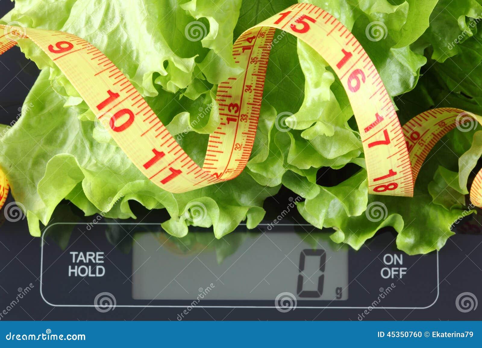 Laitue verte et ruban métrique sur l échelle de cuisine