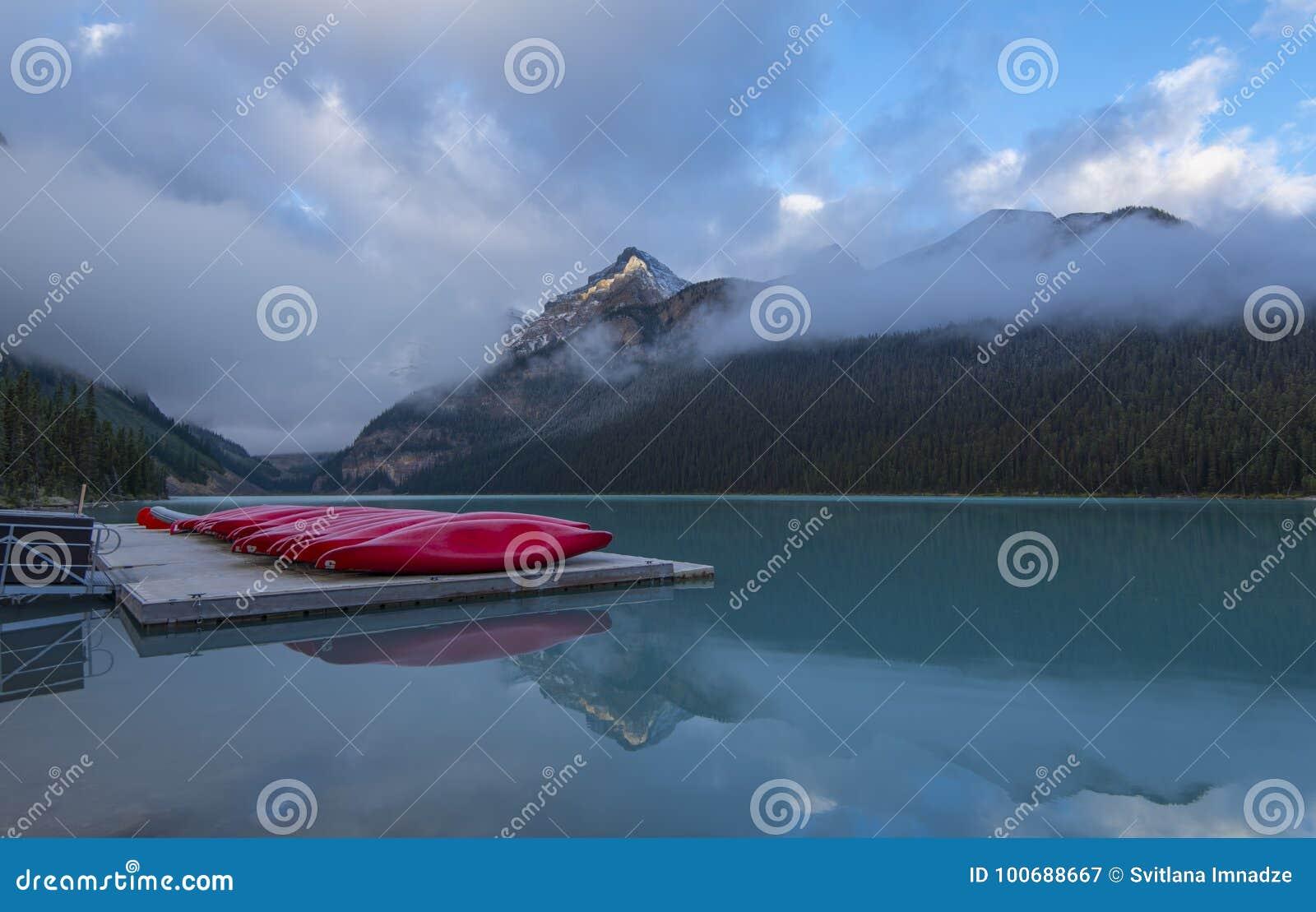 Lake Louise et canoës rouges dans le matin brumeux
