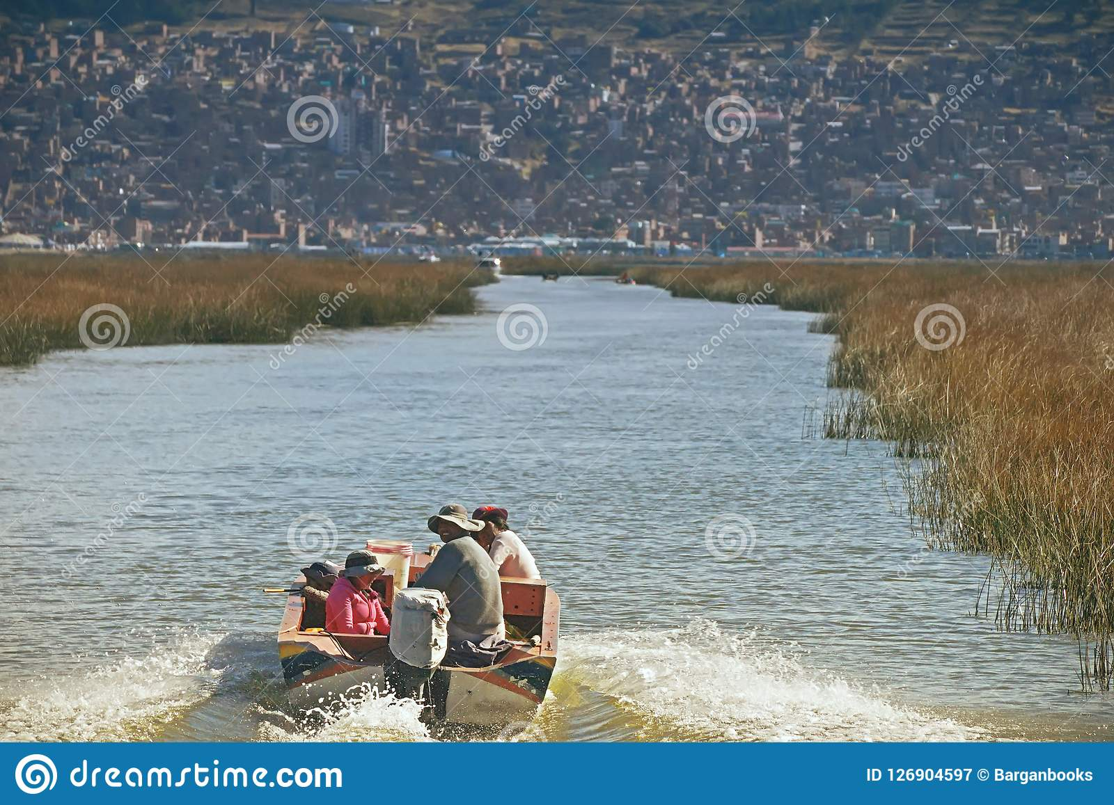 Lake Titicaca, Peru - August 17th, 2018:A peruvian family sails on Lake Titicaca, a large, deep lake in the Andes on the border of