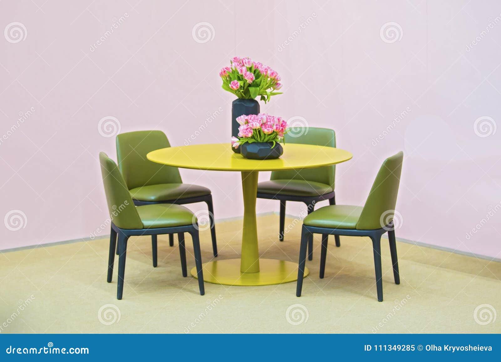 Lakonisk inre av matsalen Gula rund tabell- och gräsplanläderstolar, vas med blommor på tabellen Isolat på rosa färger