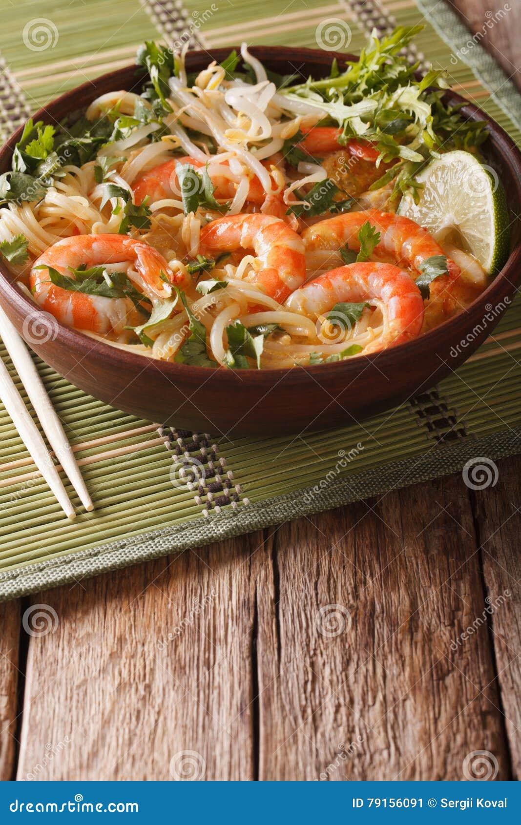 Laksa soppa med räkor, nudlar, groddar och koriander i en pilbåge