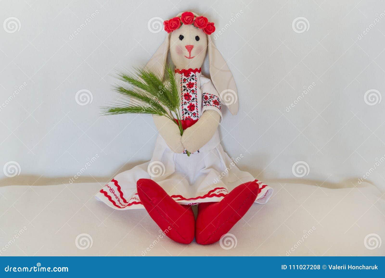 Lala w krajowym Ukraińskim ludowym kostiumu, utrzymania spikelets Handmade królika królik siedzi na lekkim tle