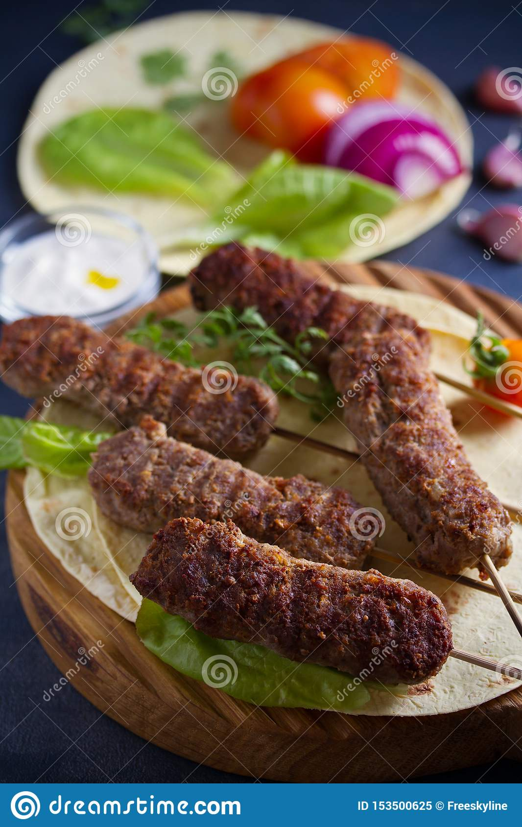 Lamb kebabs on serving board with pita bread, vegetables and yogurt sauce.