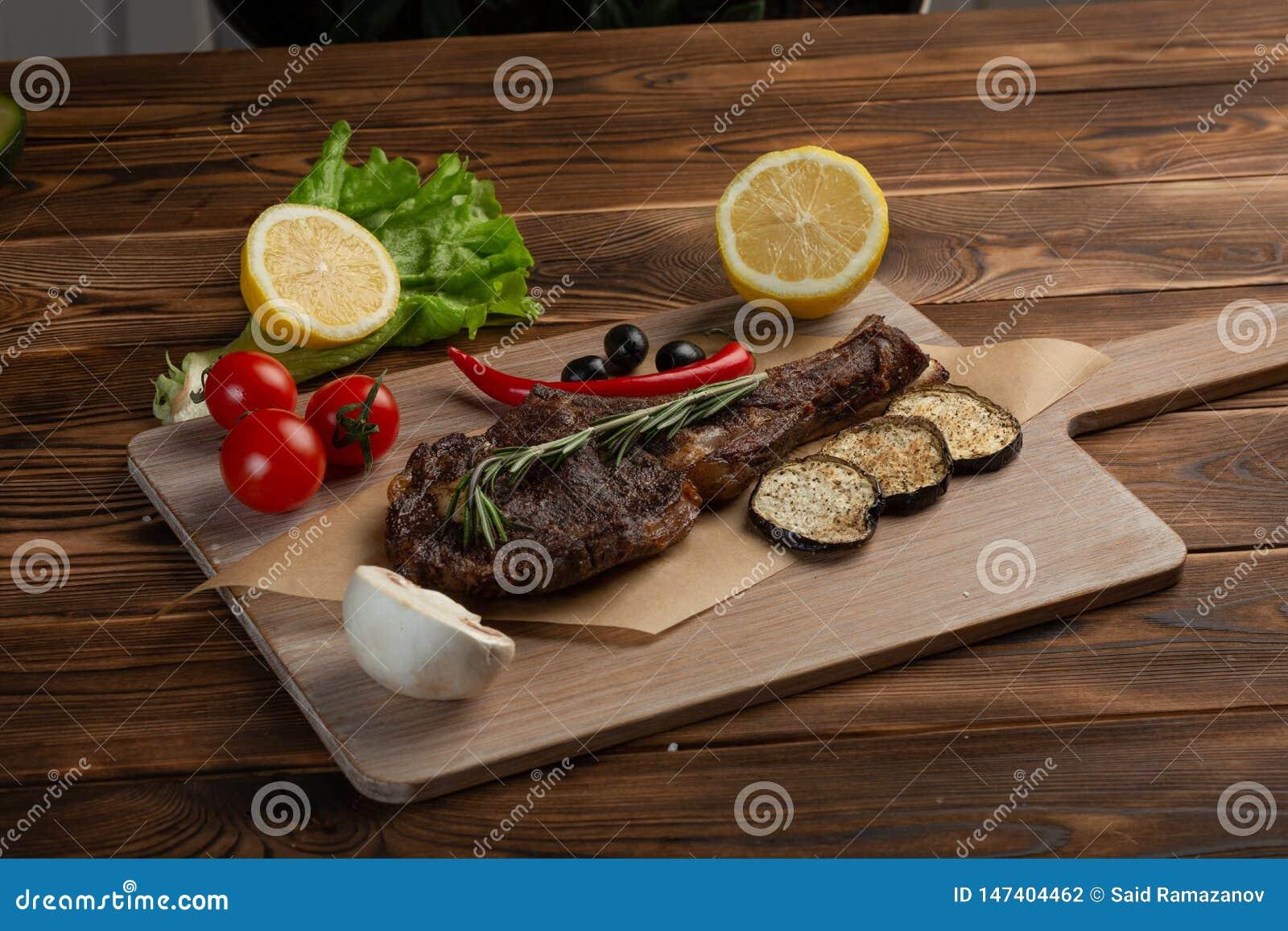 Lammbiff med gr?nsaker och tomats?s p? en tr?bakgrund