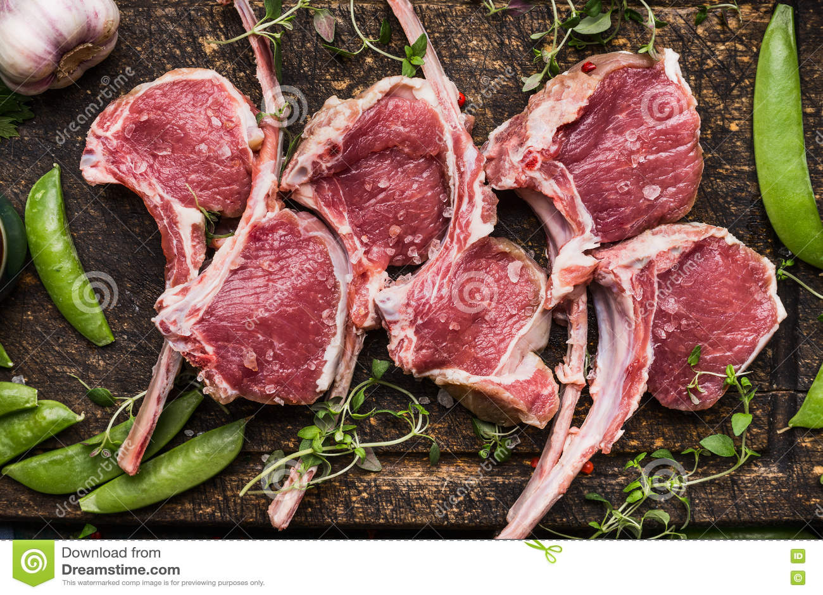 Lammkarree des rohen Fleisches und grüne Erbse auf dunklem hölzernem Hintergrund, Draufsicht