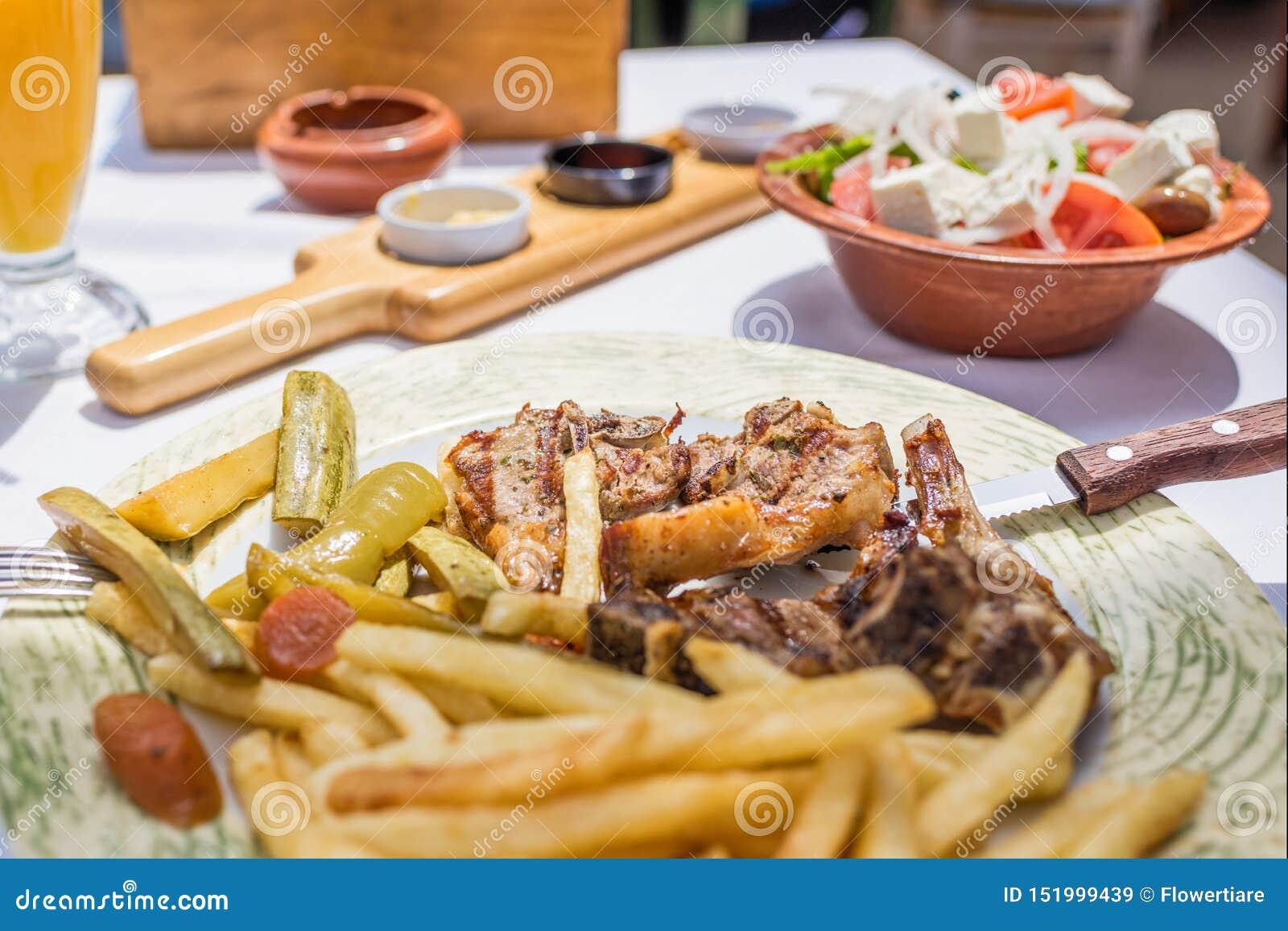 Lammkotletter med grönsaker och stekpotatisar på en platta i en grekisk restaurang eller krog