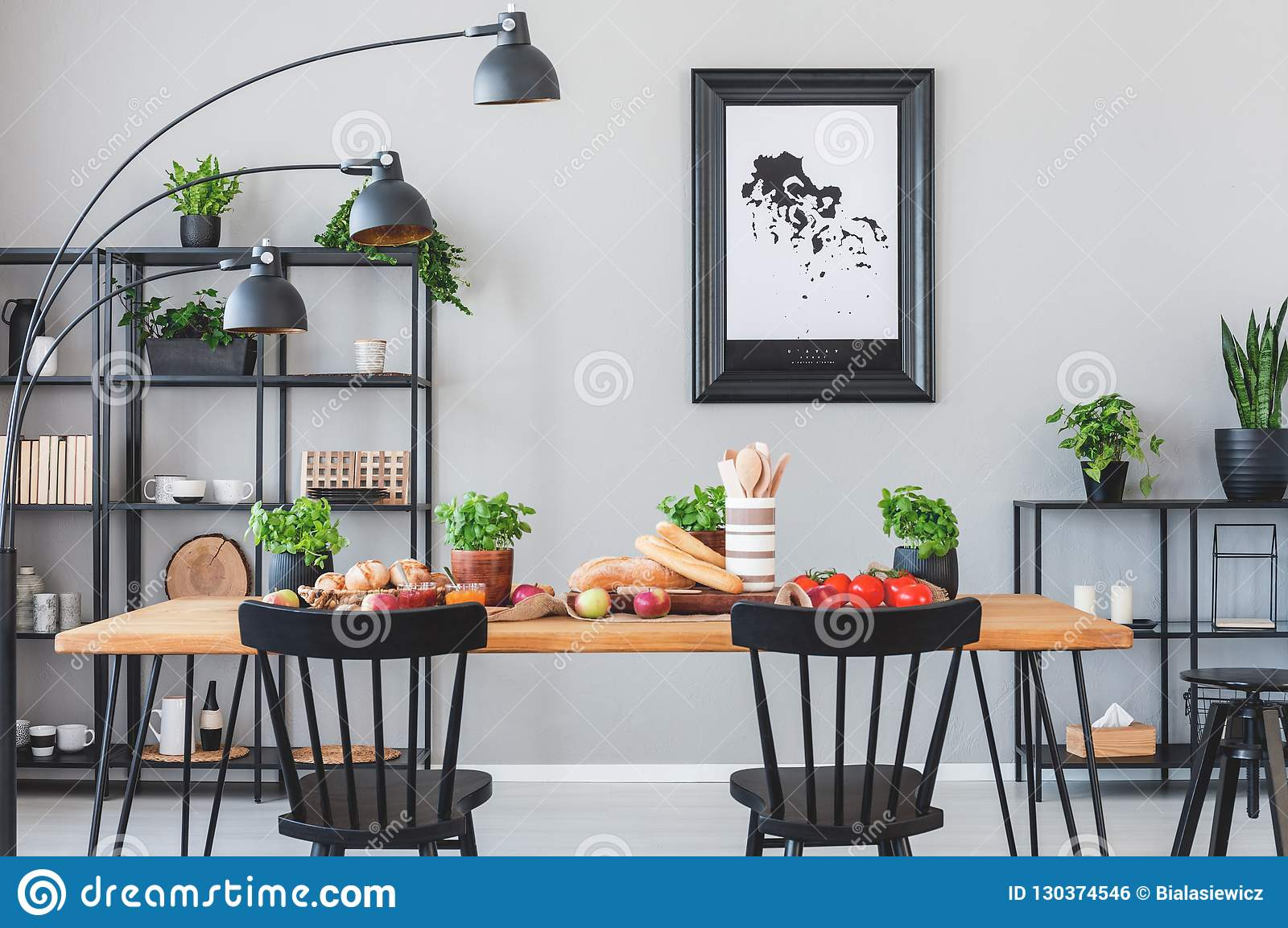 Lamp above black chairs and wooden table with food in grey dining room interior with poster