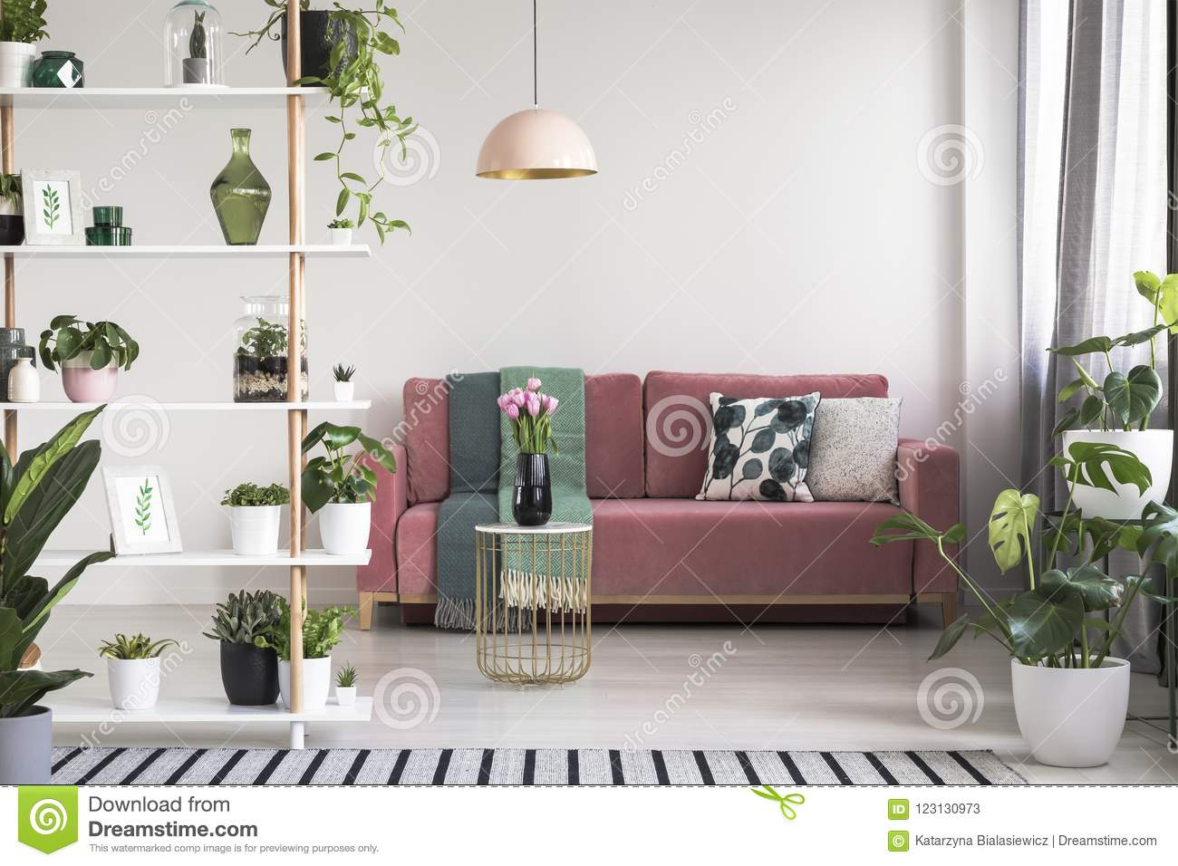 lamp above table with flowers in front of red sofa in