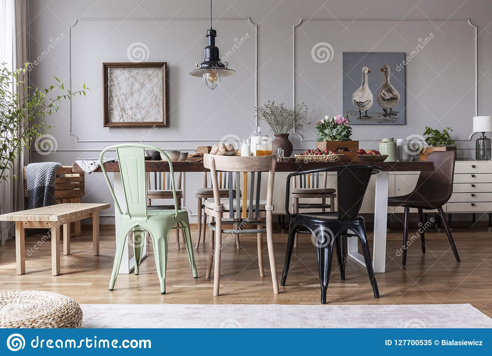 Lamp above wooden table with flowers in modern grey dining room interior with chairs. Real photo