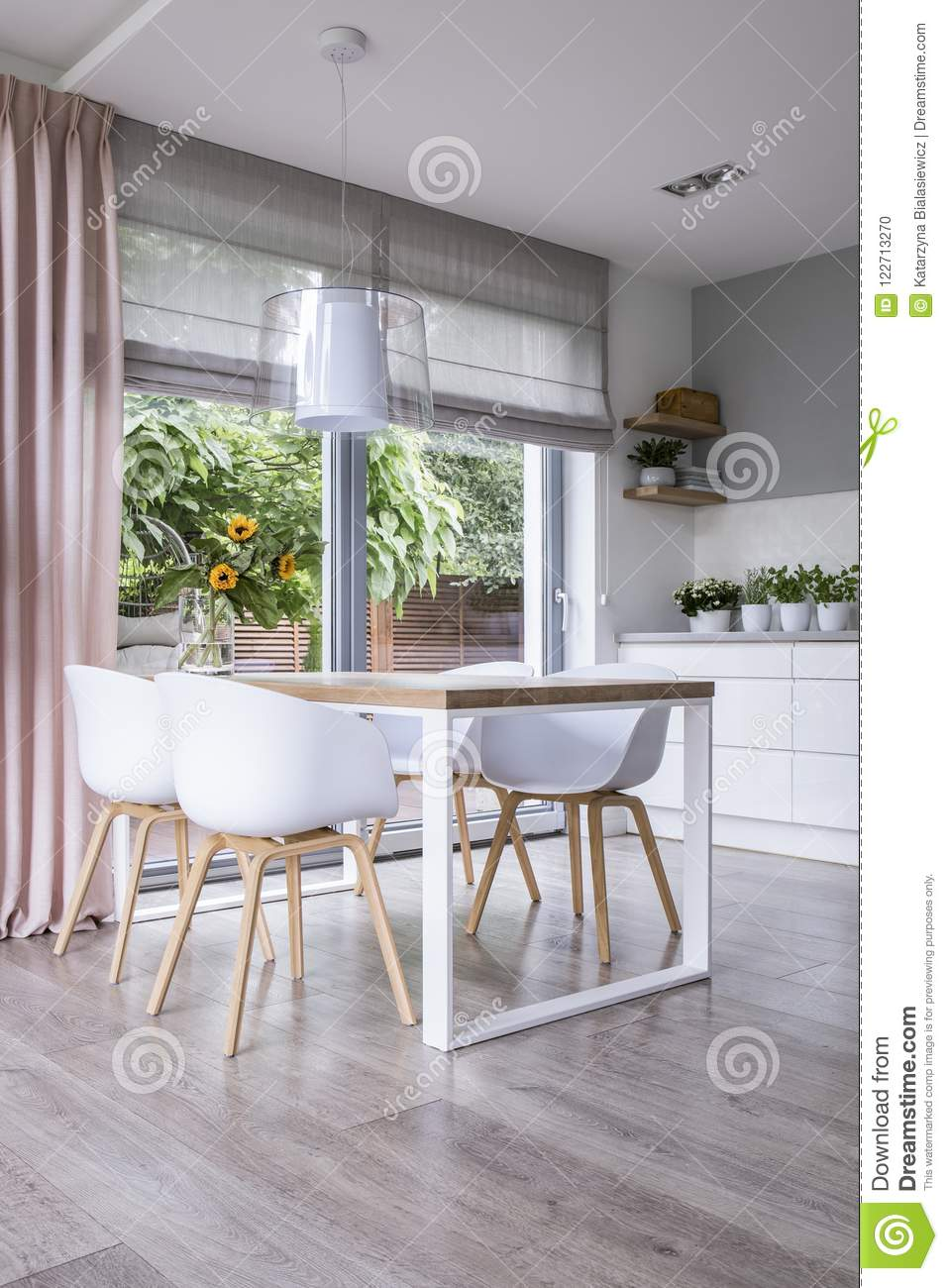 Lamp Above Wooden Table And White Chairs In Dining Room Interior With Drapes Window