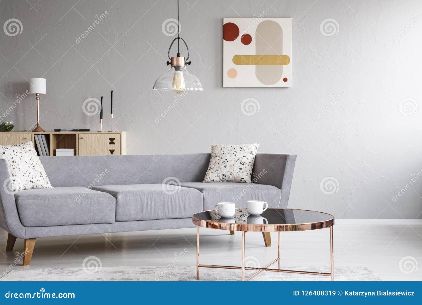 Lamp boven grijze sofa met kussens in helder woonkamerbinnenland met affiche en lijst Echte foto