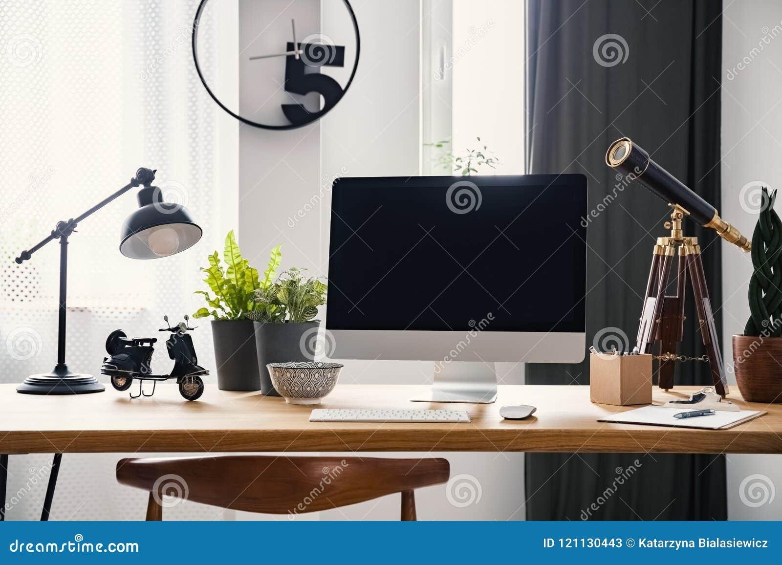Lampa i komputer stacjonarny na drewnianym biurku w nowożytnym freelancer ` s