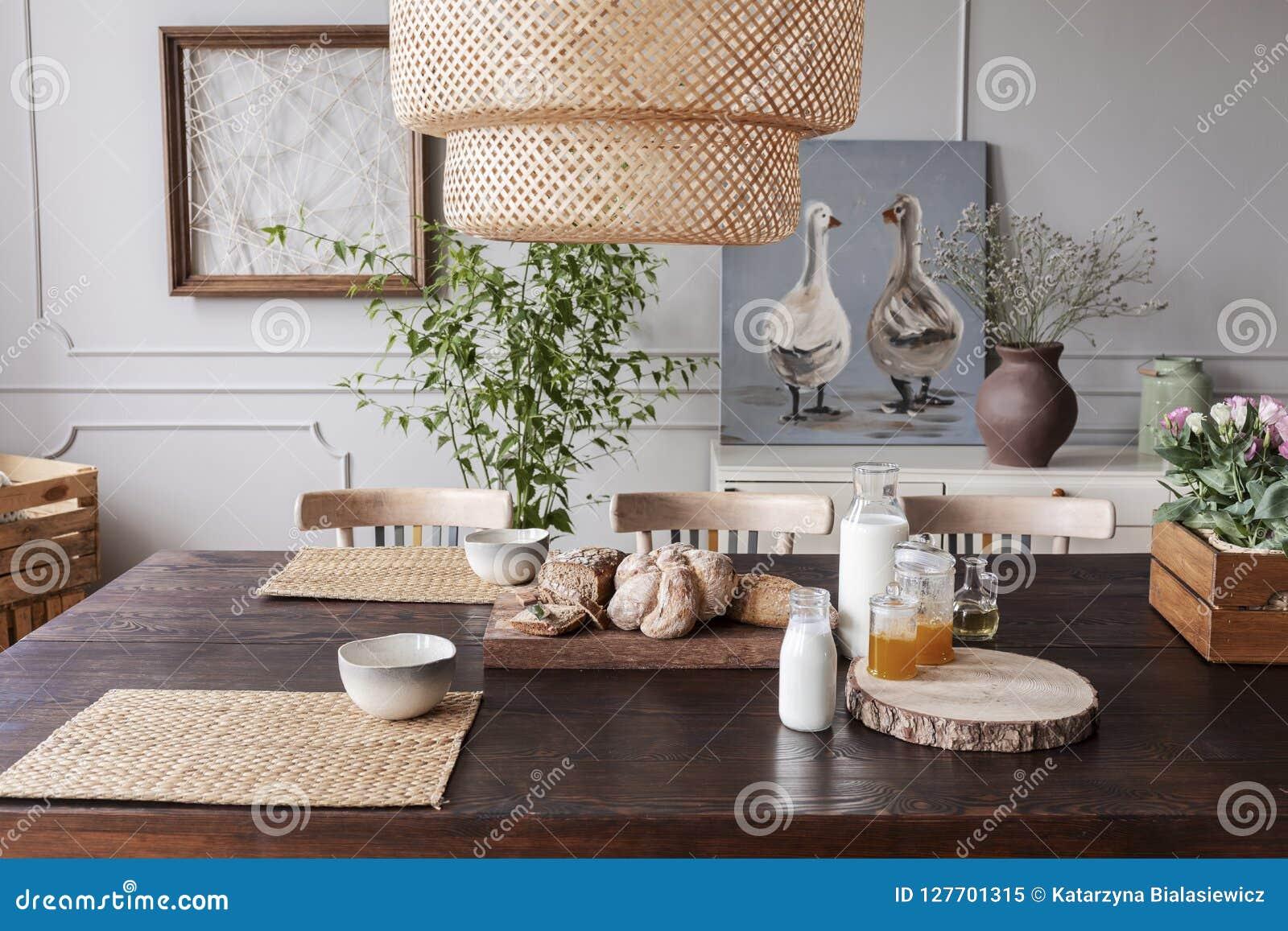 Lampa ovanför trätabellen med mat och bunkar i grå matsalinre med affischer Verkligt foto