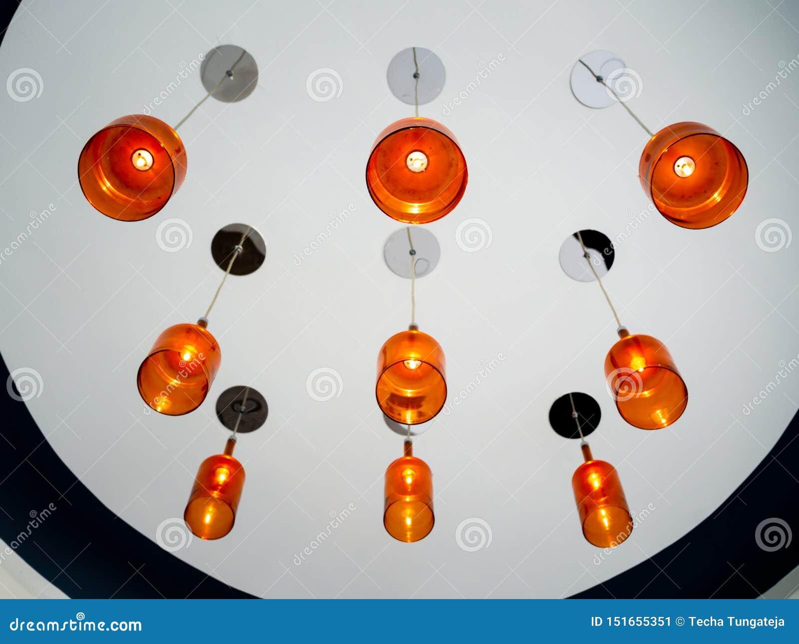 Lampada arancio moderna del soffitto che pende dal soffitto bianco Accensione del concetto della decorazione