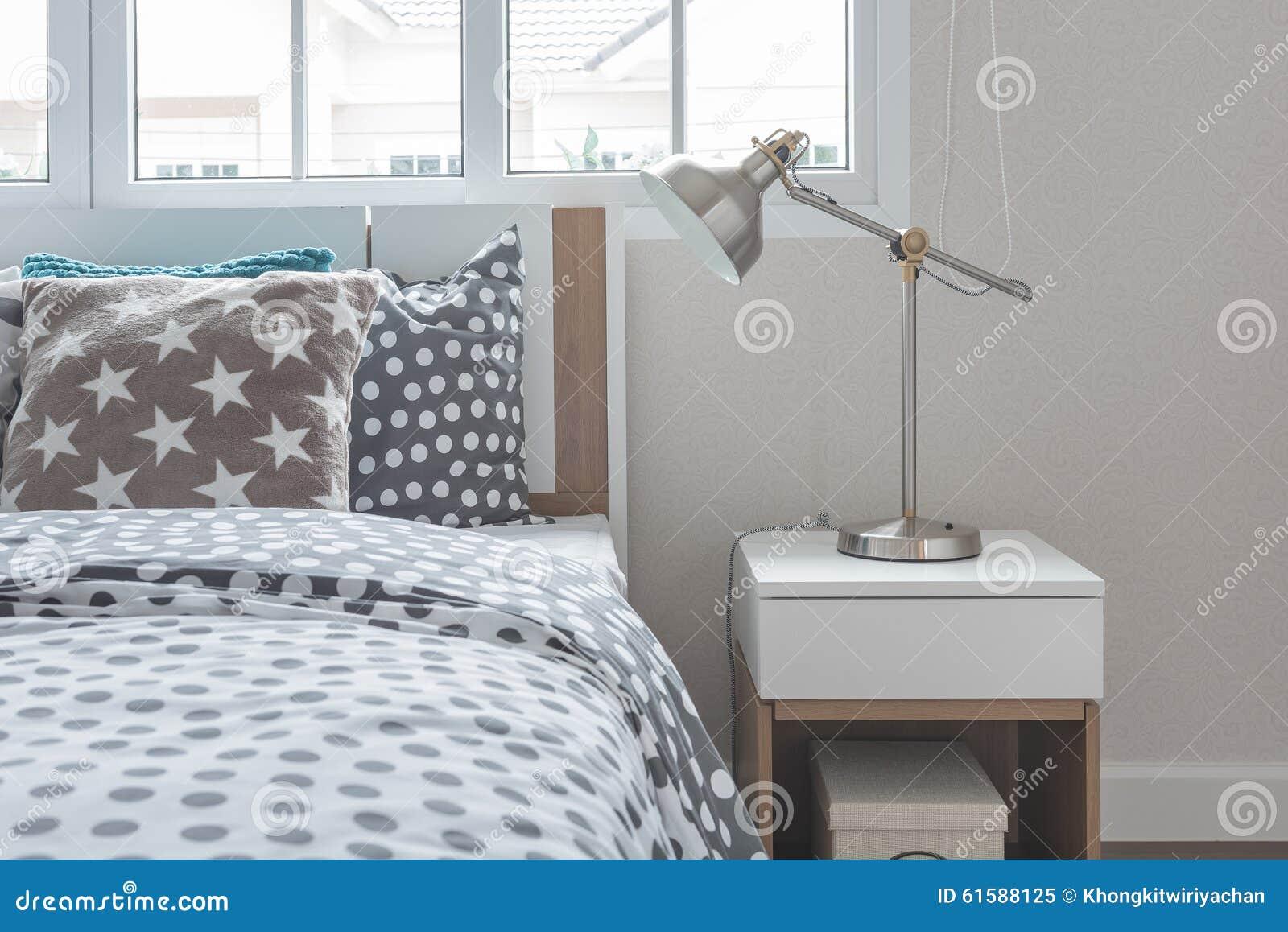 Lampada moderna sul comodino con il letto di legno immagine stock