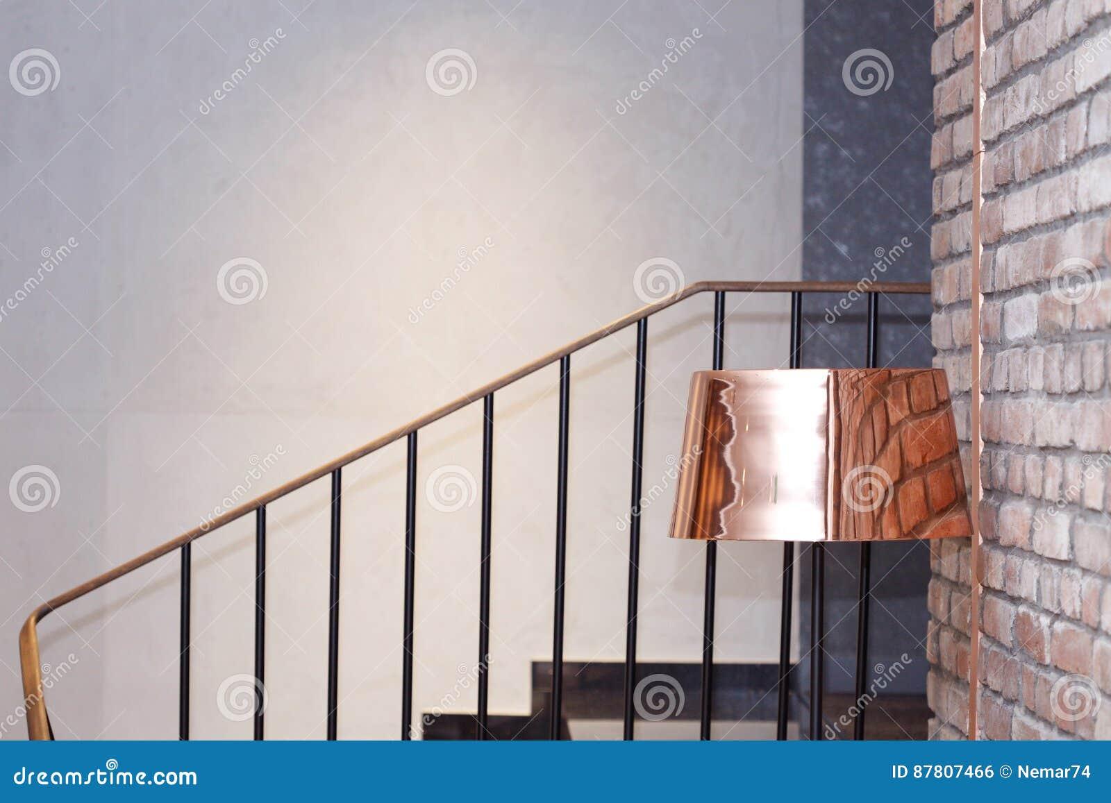 Lampadaire en laiton à côté d un mur de briques près des escaliers