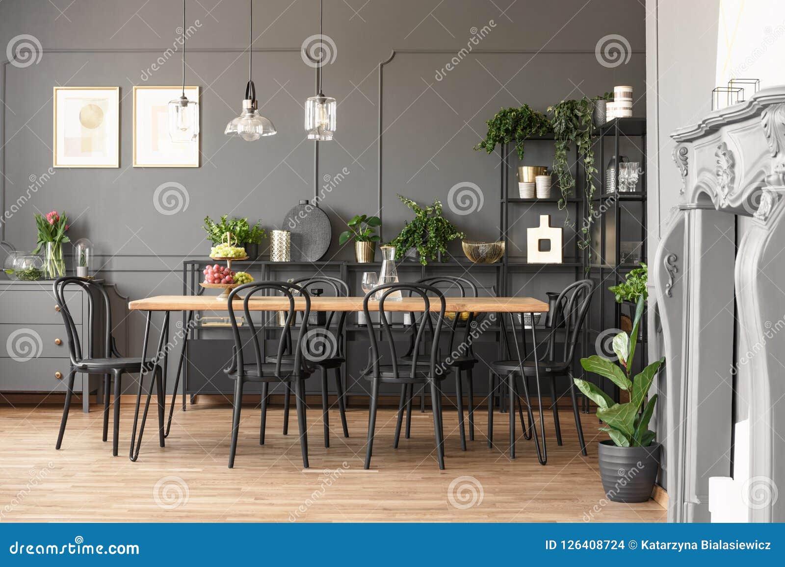 Lampade Sopra Tavolo Da Pranzo lampade sopra la tavola di legno e sedie nere nella sala da
