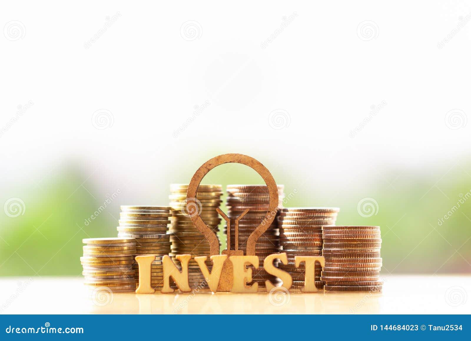 Lampadina e pila di monete nel concetto del risparmio e di crescita dei soldi o dei risparmi di energia