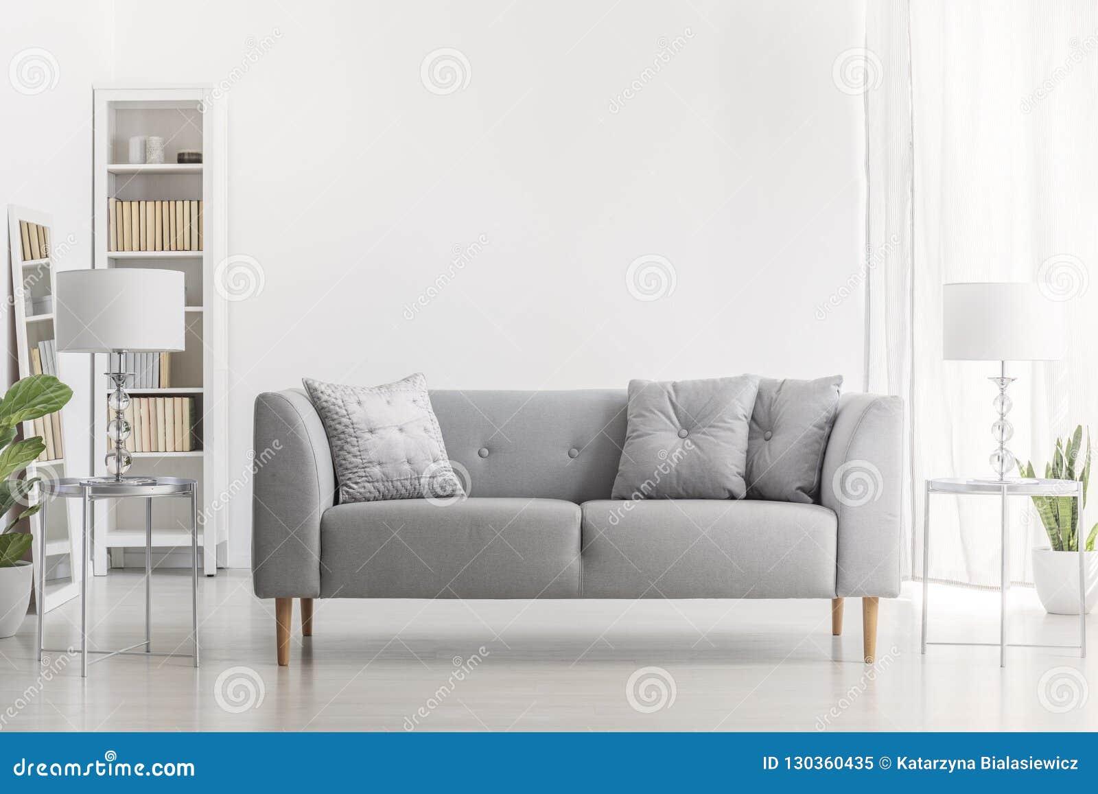 Lampan på försilvrar tabellen bredvid den gråa soffan med kuddar i vit vardagsrum som är inre med växten Verkligt foto
