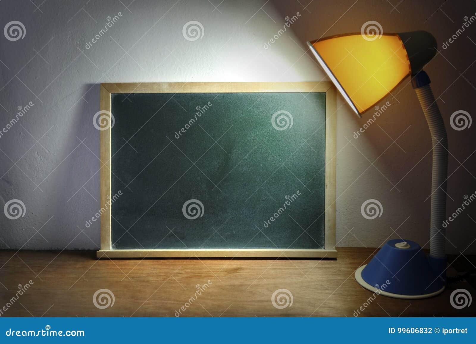 Lampe de bureau brillant sur le tableau noir photo stock image