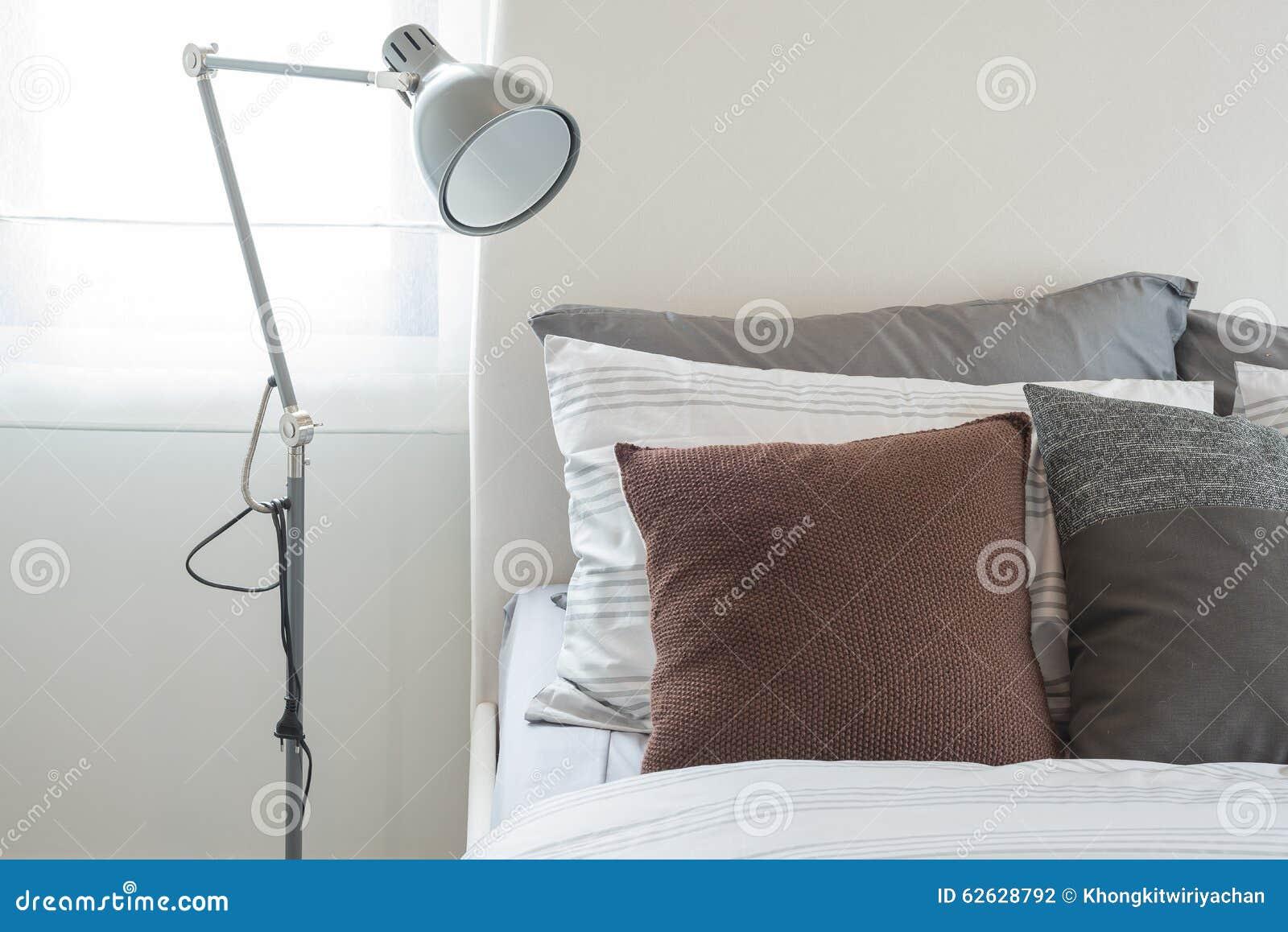 Lampe grise moderne dans la chambre à coucher moderne avec l oreiller brun