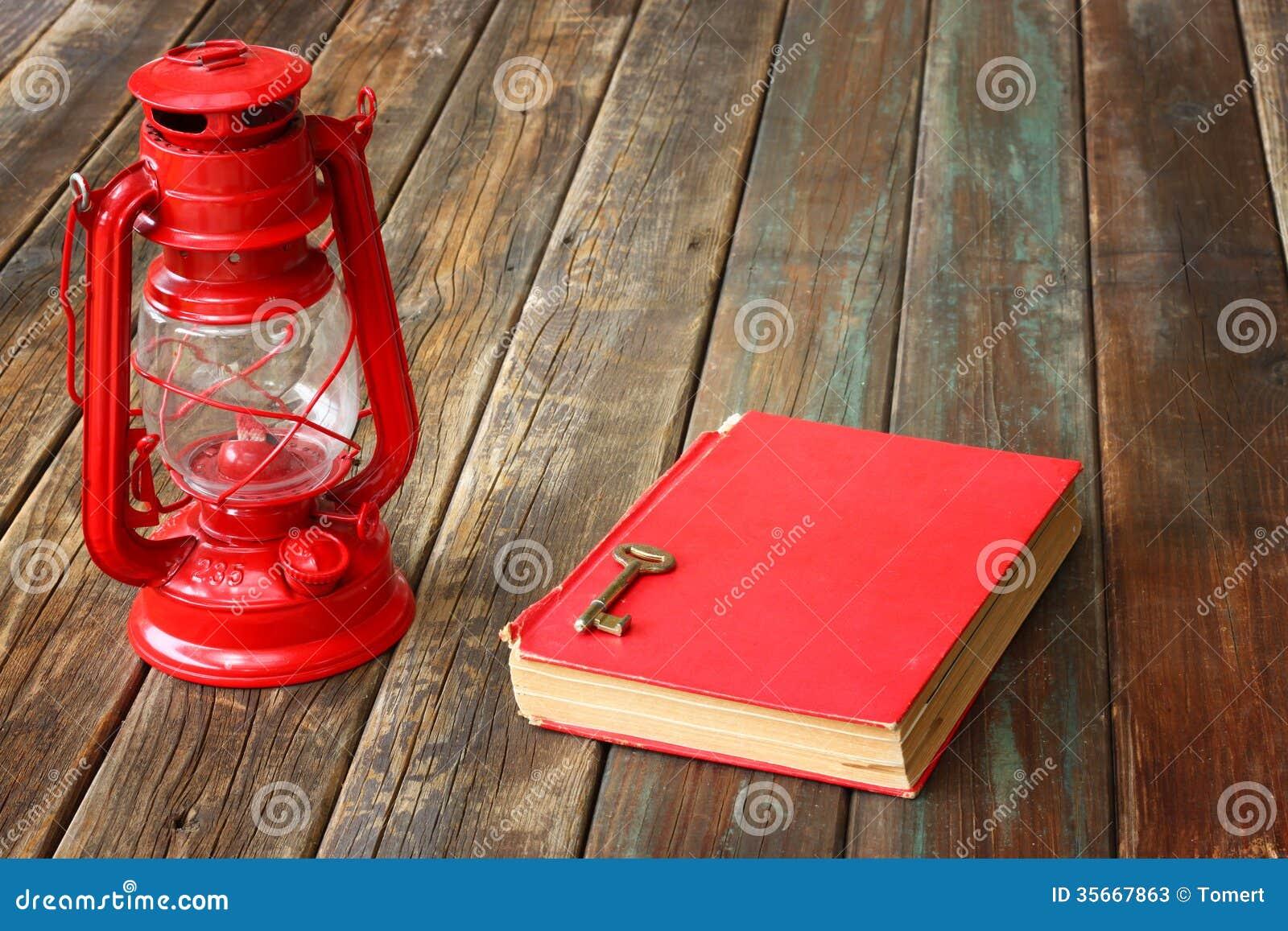 lampe rouge de vintage et livre antique rouge sur la table en bois de vintage toujours. Black Bedroom Furniture Sets. Home Design Ideas