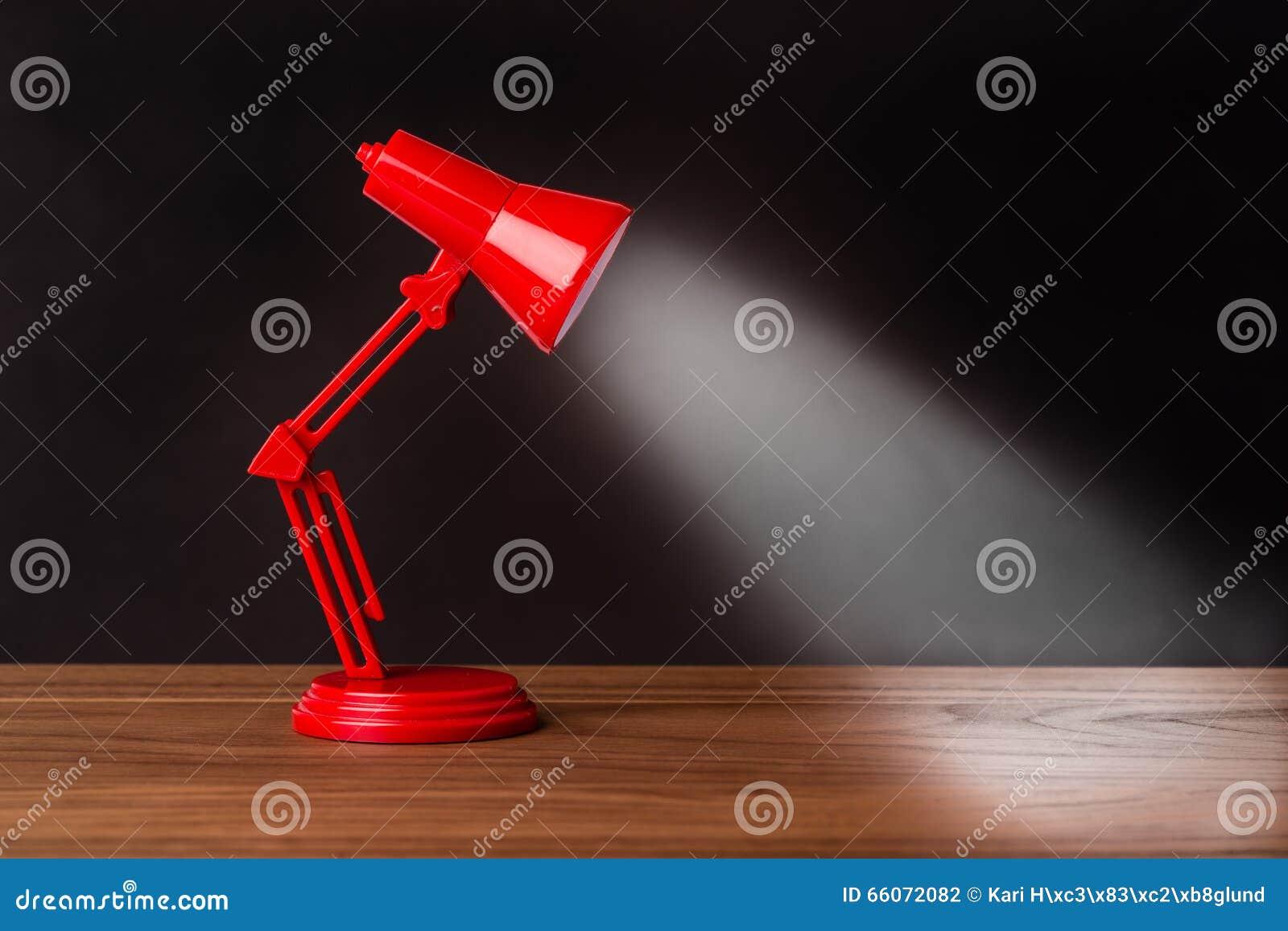 Lampe rouge en métal sur un bureau en bois avec le fond noir photo