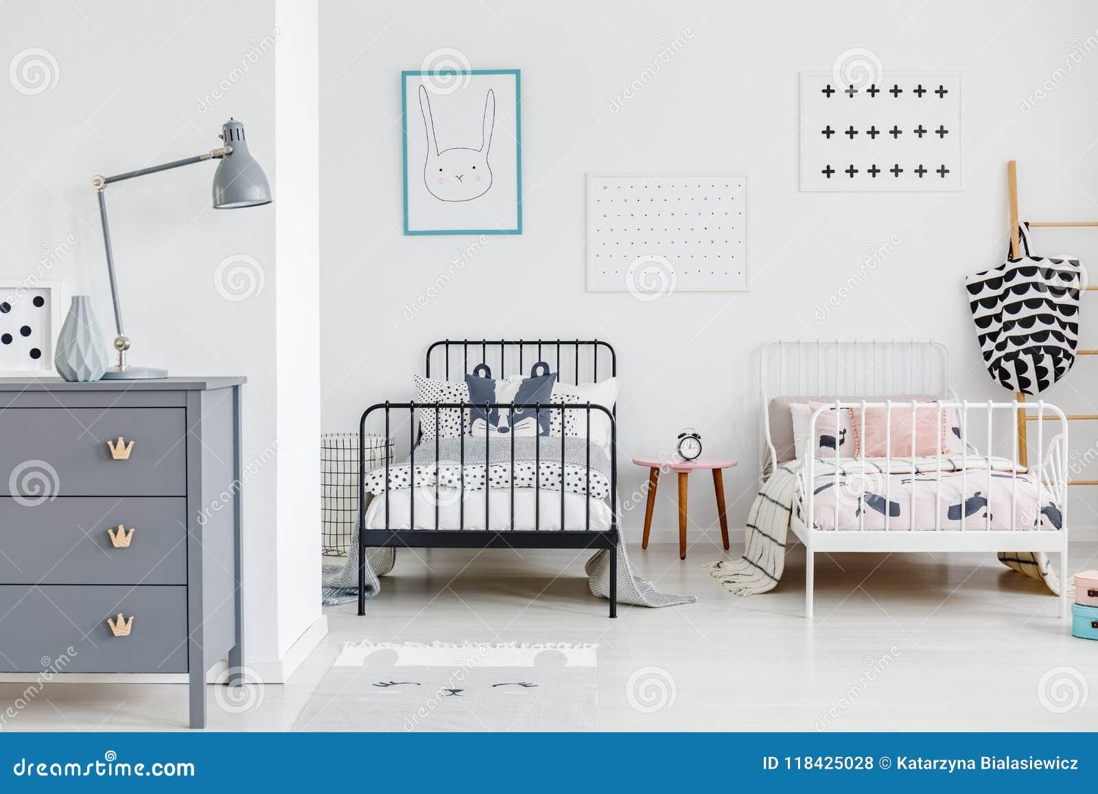 Lampe sur le coffret gris dans l intérieur lumineux de chambre à coucher d enfants avec le bl
