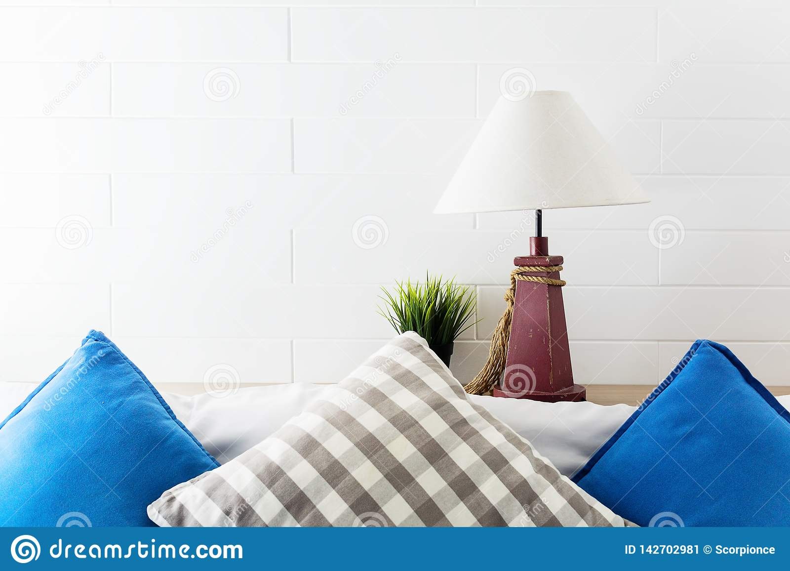 Lampe und Grünpflanze auf Kopfende mit den blauen und grauen pollows Hotelzimmerinnenhintergrund