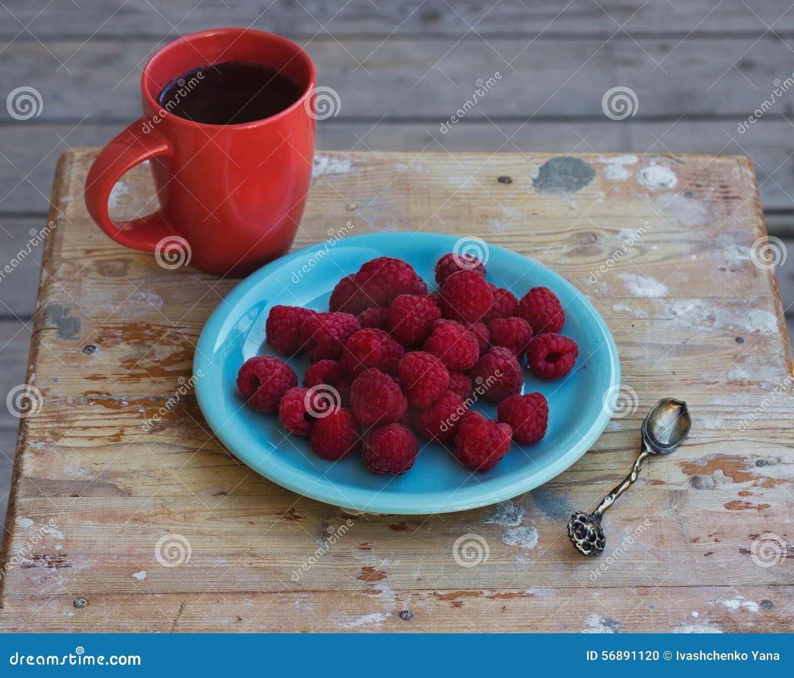Lamponi su un piatto con una tazza di caffè