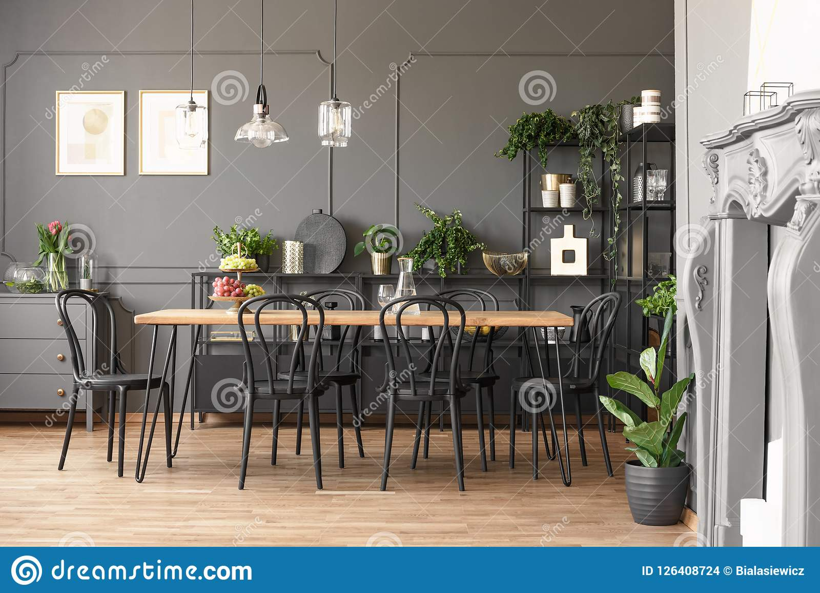 Lamps above wooden table and black chairs in grey dining room in