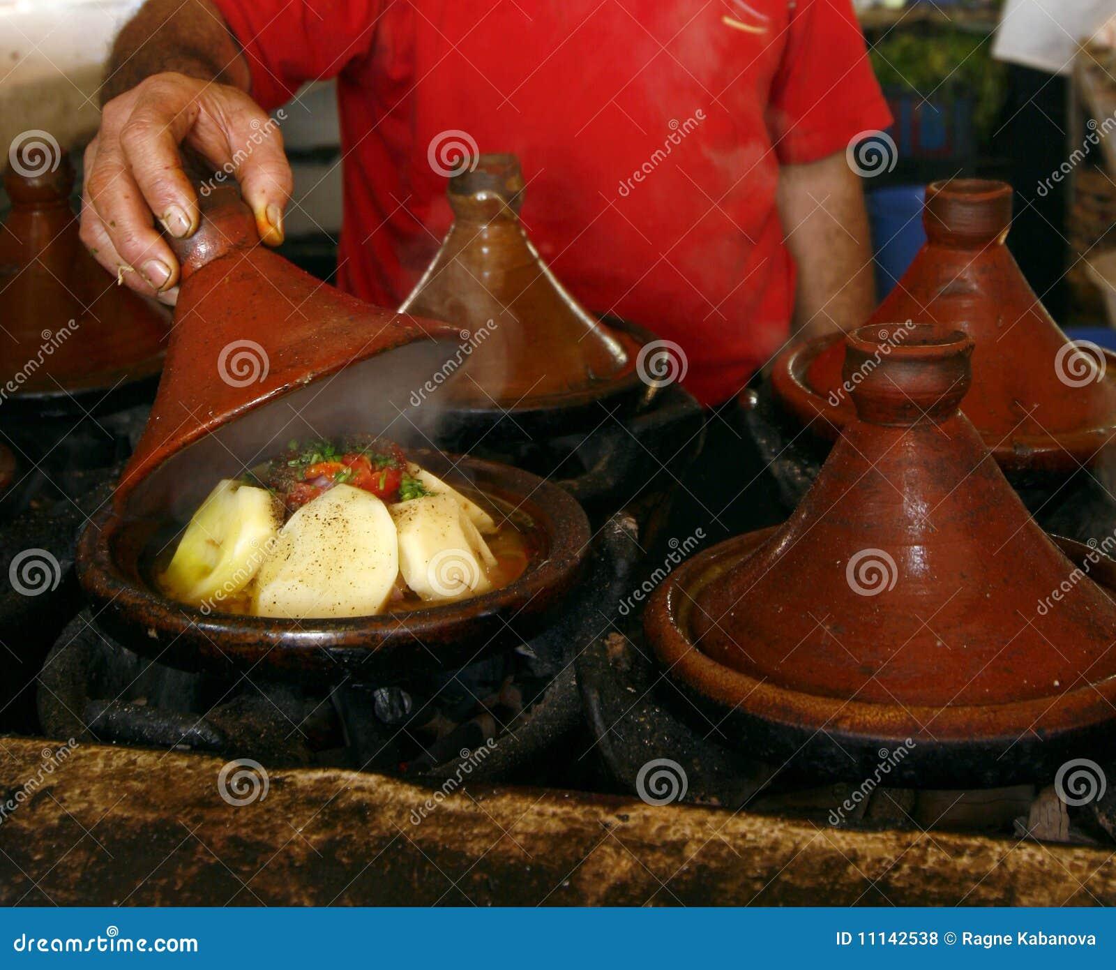Lancez le cuisinier sur le marché retenant un cache d un tajine, Maroc
