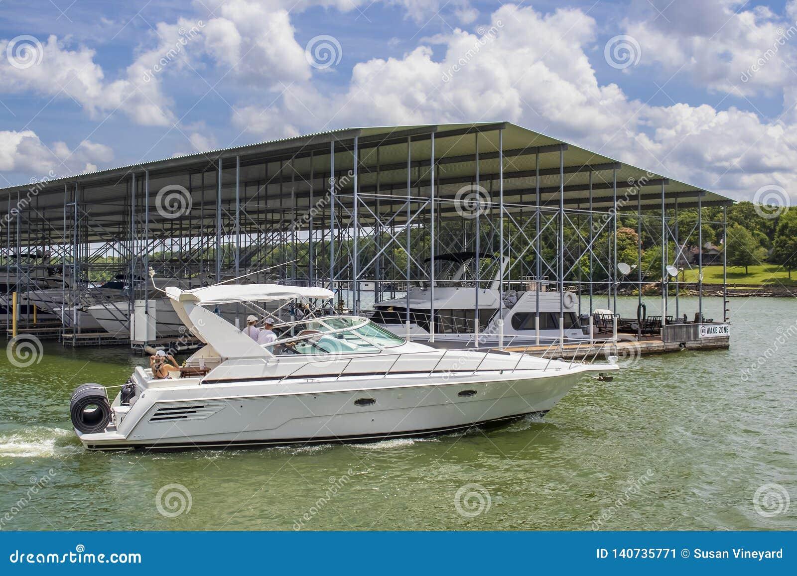 Lancha luxuosa com floatie rolado na parte traseira no lago no verão que passa pela doca coberta do barco com os barcos mais extr