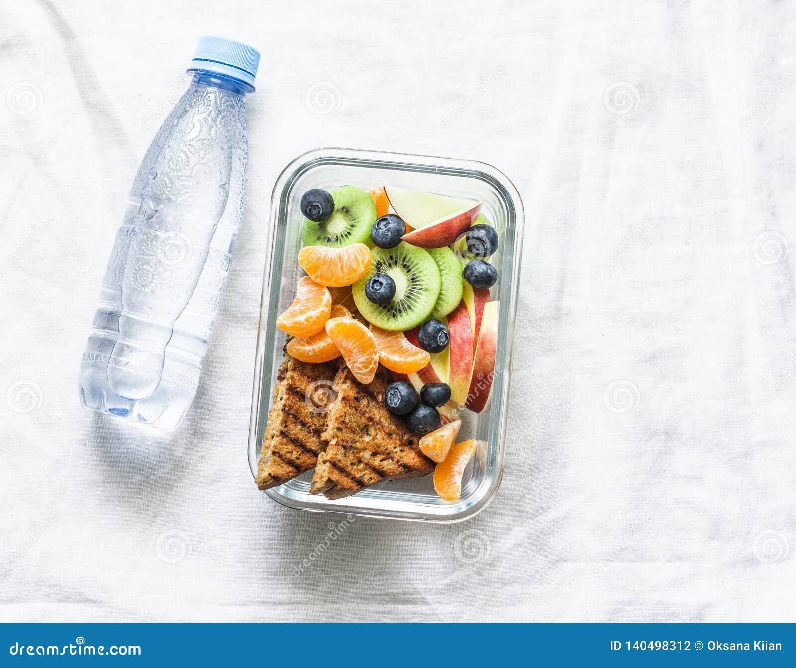 Lancheira da vitamina do petisco saudável do alimento e garrafa doces da agua potável em um fundo claro Brinde da manteiga de ame