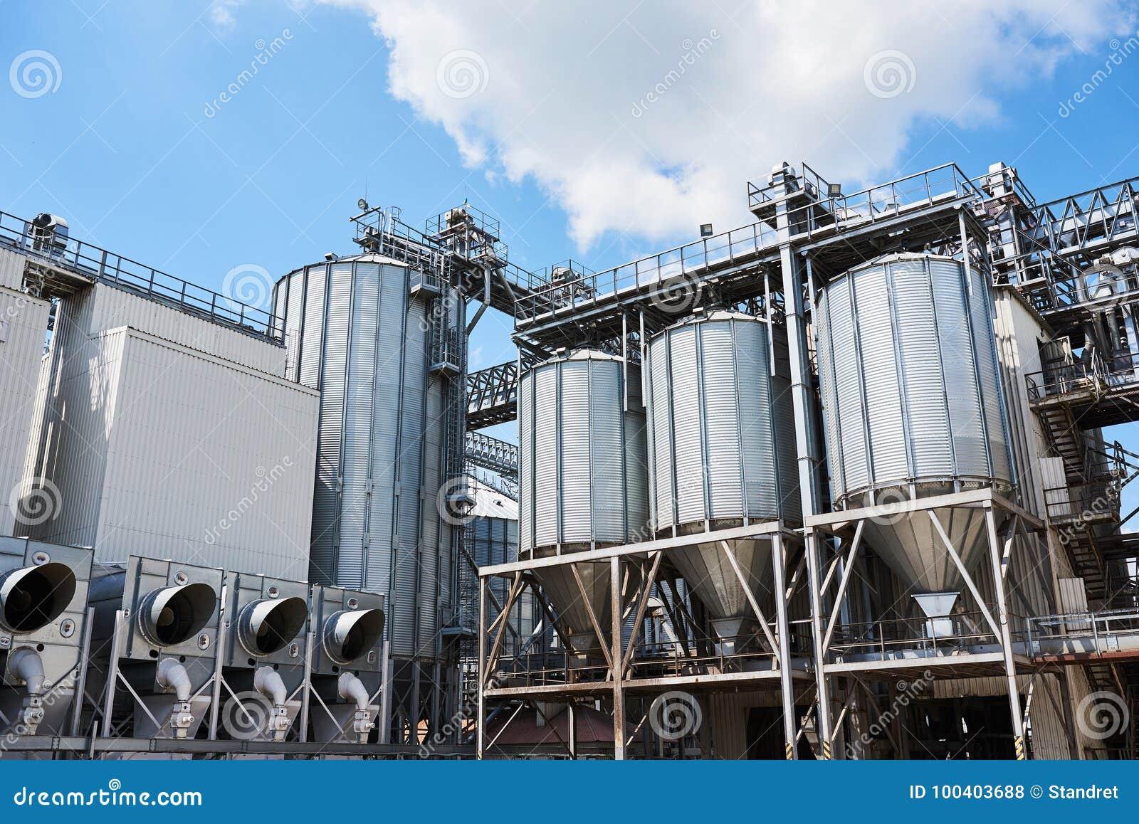 Landbouw silo s De Buitenkant van de bouw Opslag en het drogen van korrels, tarwe, graan, soja, zonnebloem tegen de blauwe hemel