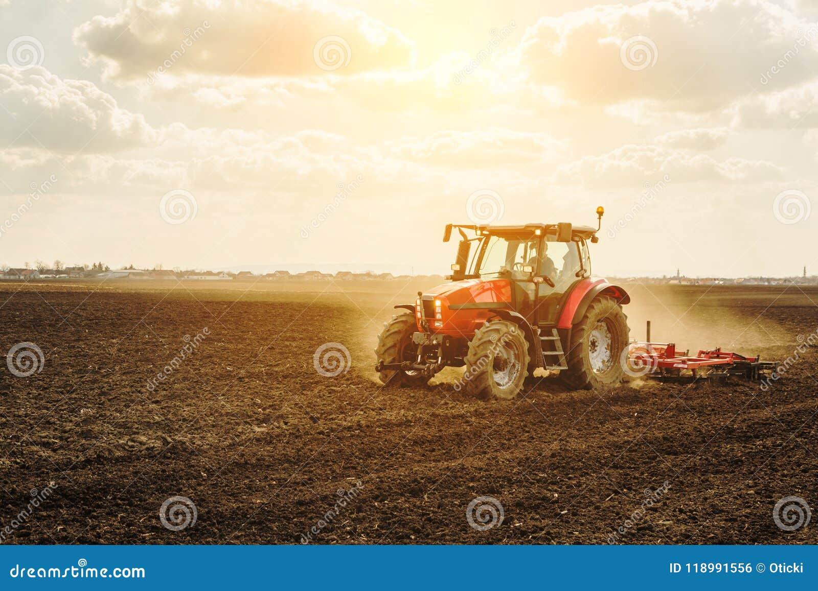 Landbouwer die in tractor land met zaadbedlandbouwer voorbereiden