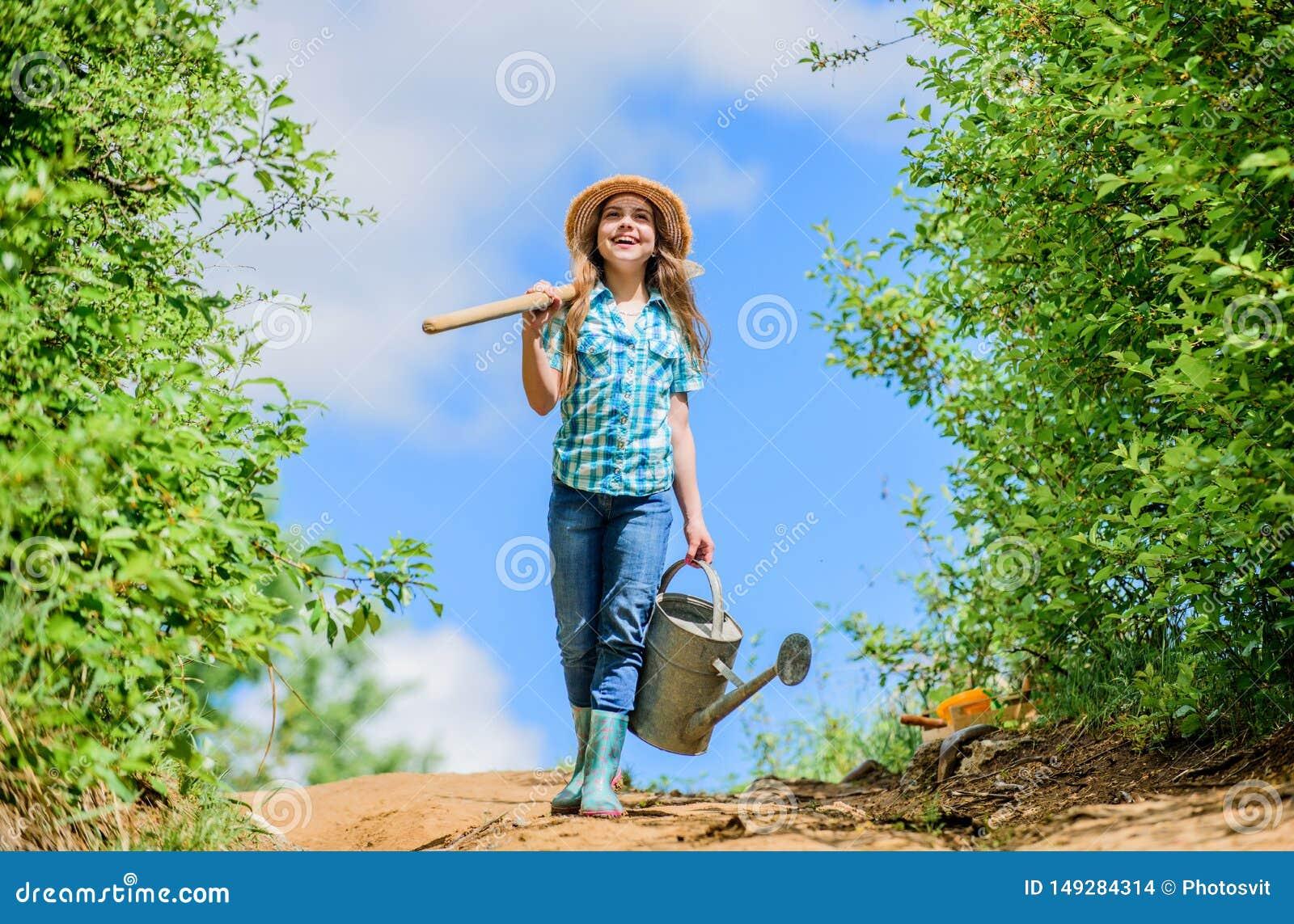 Landbouwersmeisje tuinhulpmiddelen, schop en gieter zonnige openlucht van de jong geitjearbeider Familie het plakken de kant van