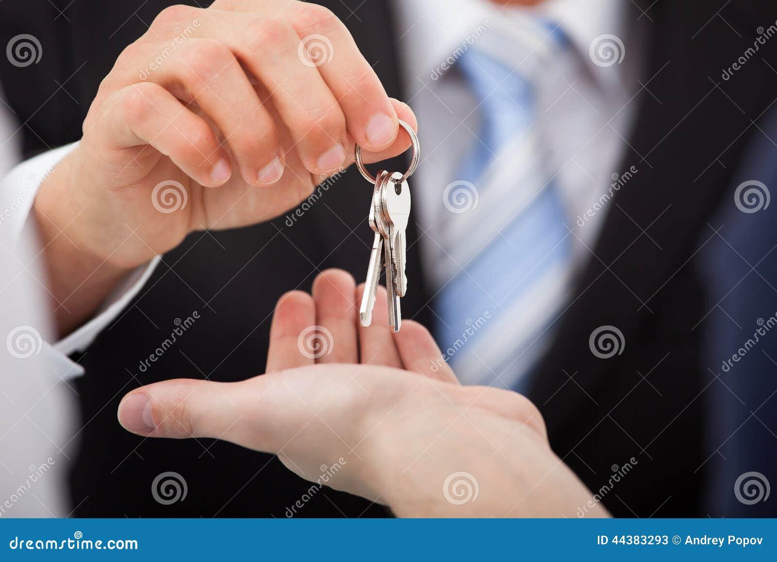 Landgoedagent die huissleutels geven aan de mens