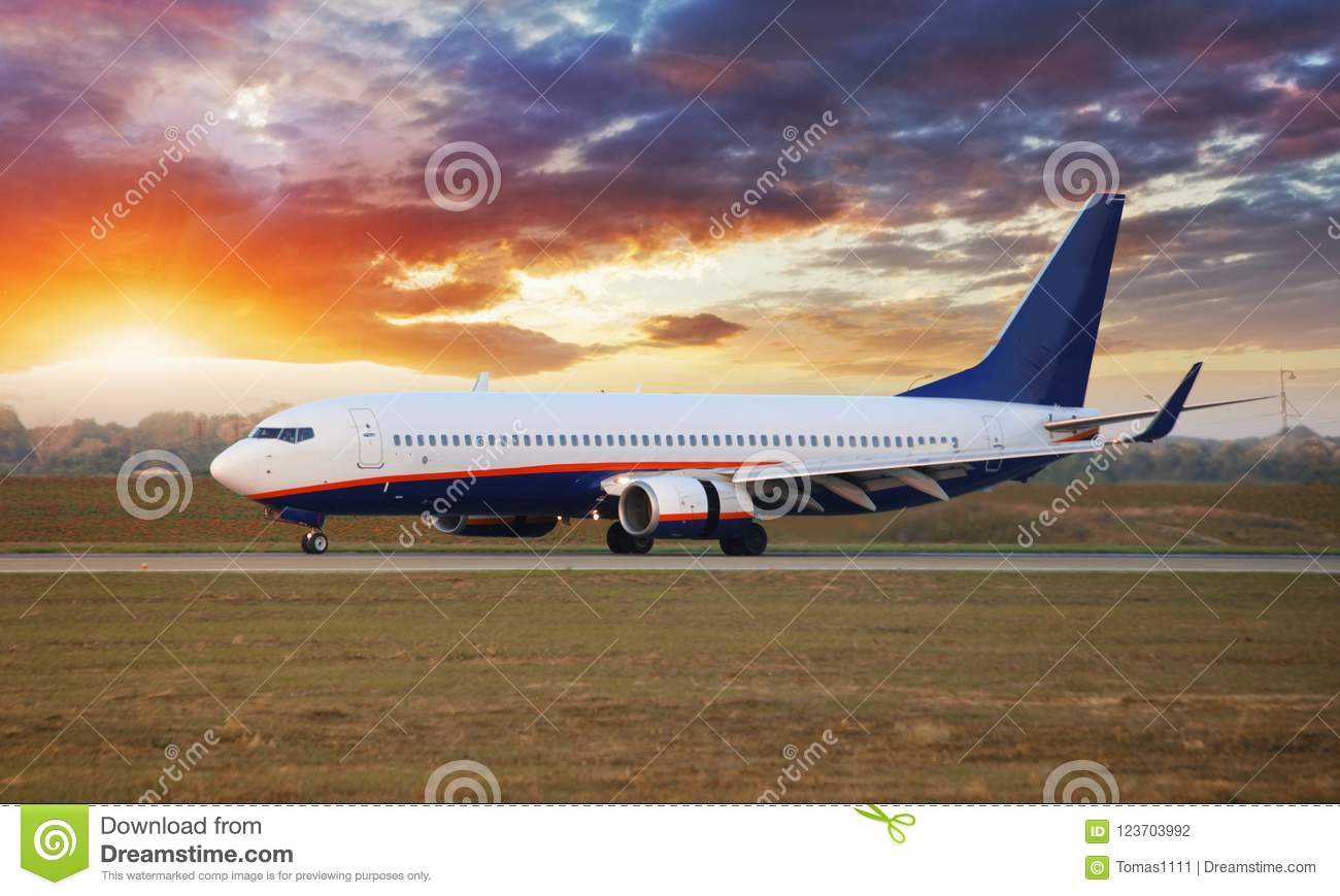 Landing airplane in Airport at sunset