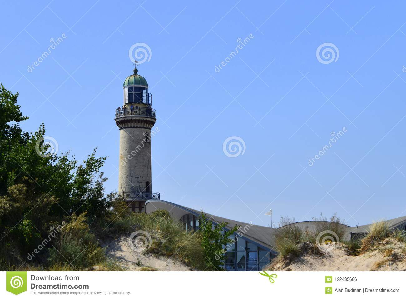 24e66434519bb Warnemunde, Germany - June 8, 2018: Landmark lighthouse and shops in beach  town of Warnemunde, Germany as seen from the beach on this date