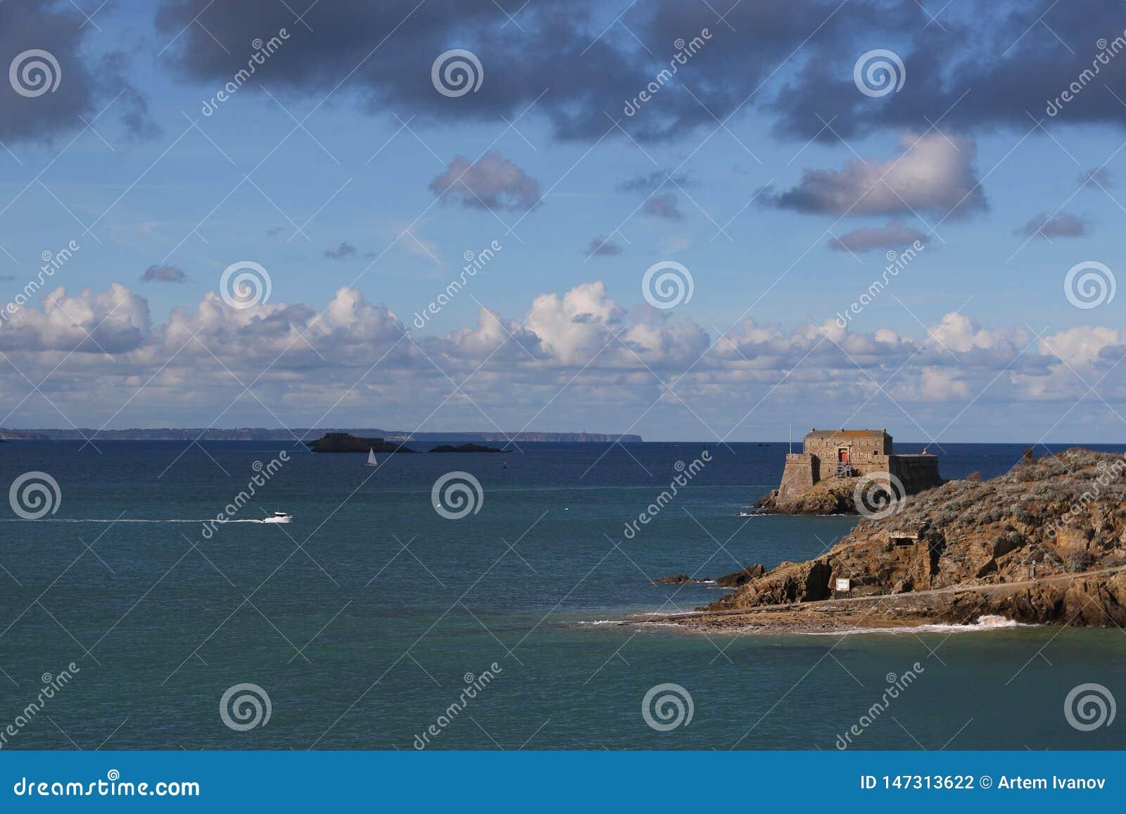 Landsape do mar com o barco a motor branco perto de Saint Malo