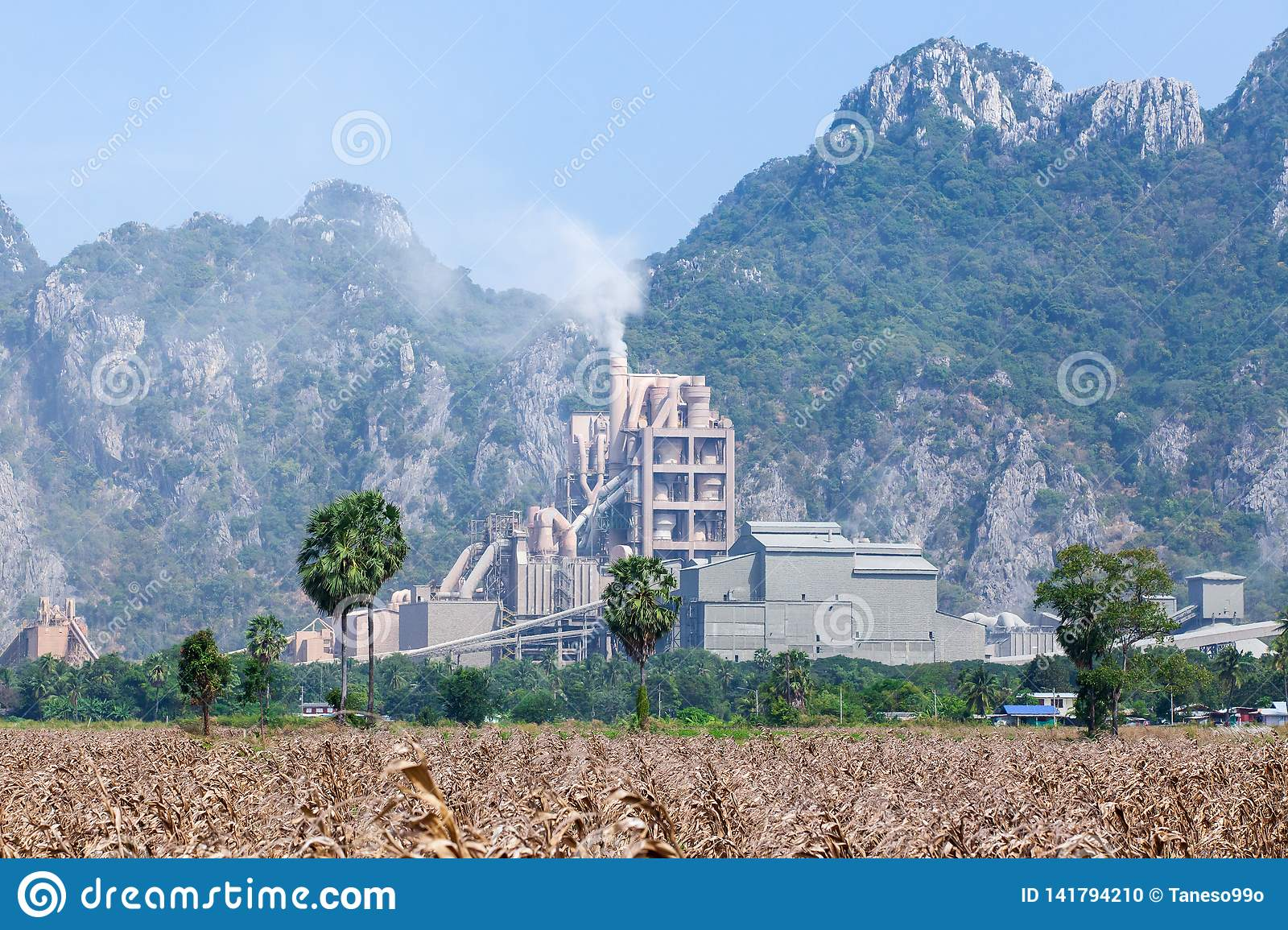 Landscape of cement factory in thailand, corn fields foregrounds, limestone mountain range backgrounds