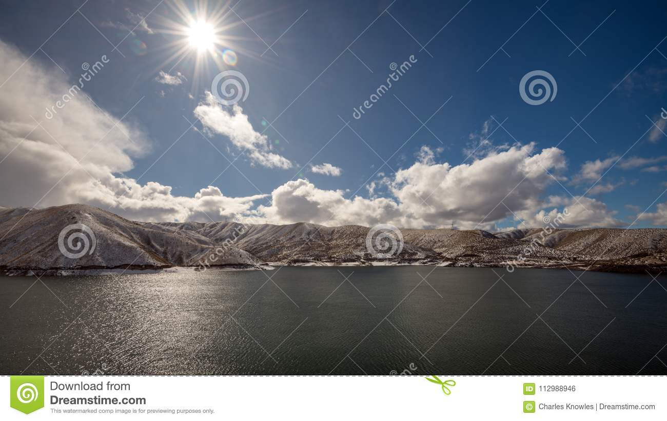 Sun star over Lucky Peak reservoir with snow and clouds
