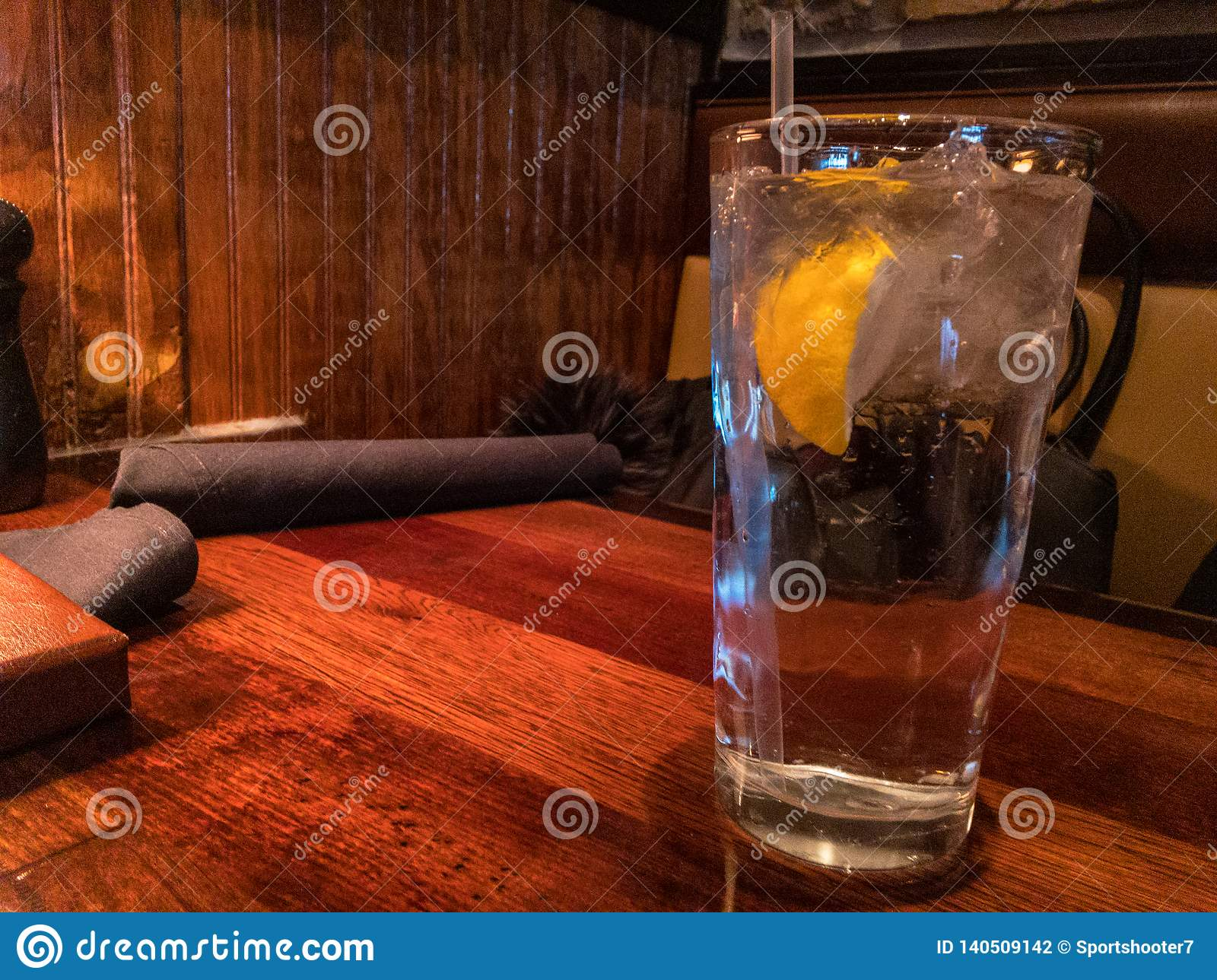 Ice water with lemon and straw on table in restaurant setting.