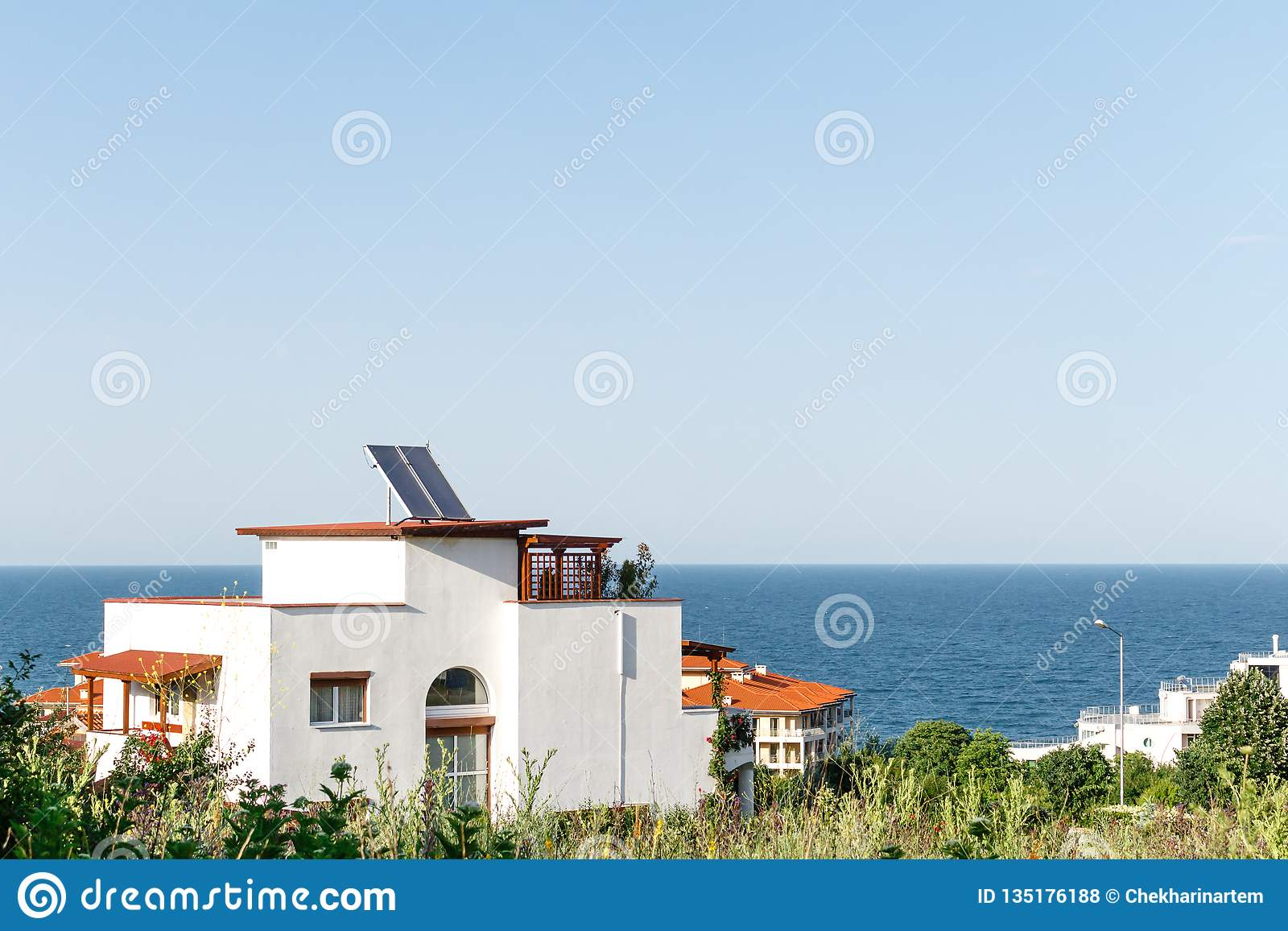 White house with solar water heating panel on the roof and sea background against blue sky. Byala, Bulgaria.