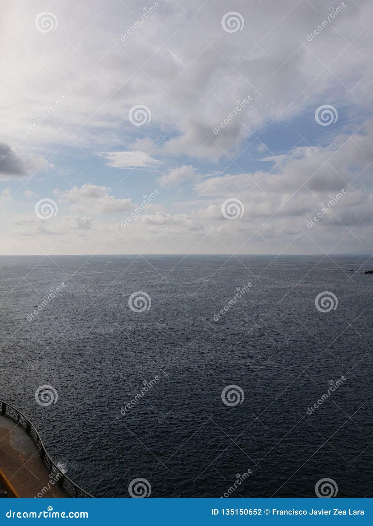 Landschaft mit dem Horizont zwischen dem Meer und dem blauen Himmel mit weißen Wolken in Acapulco
