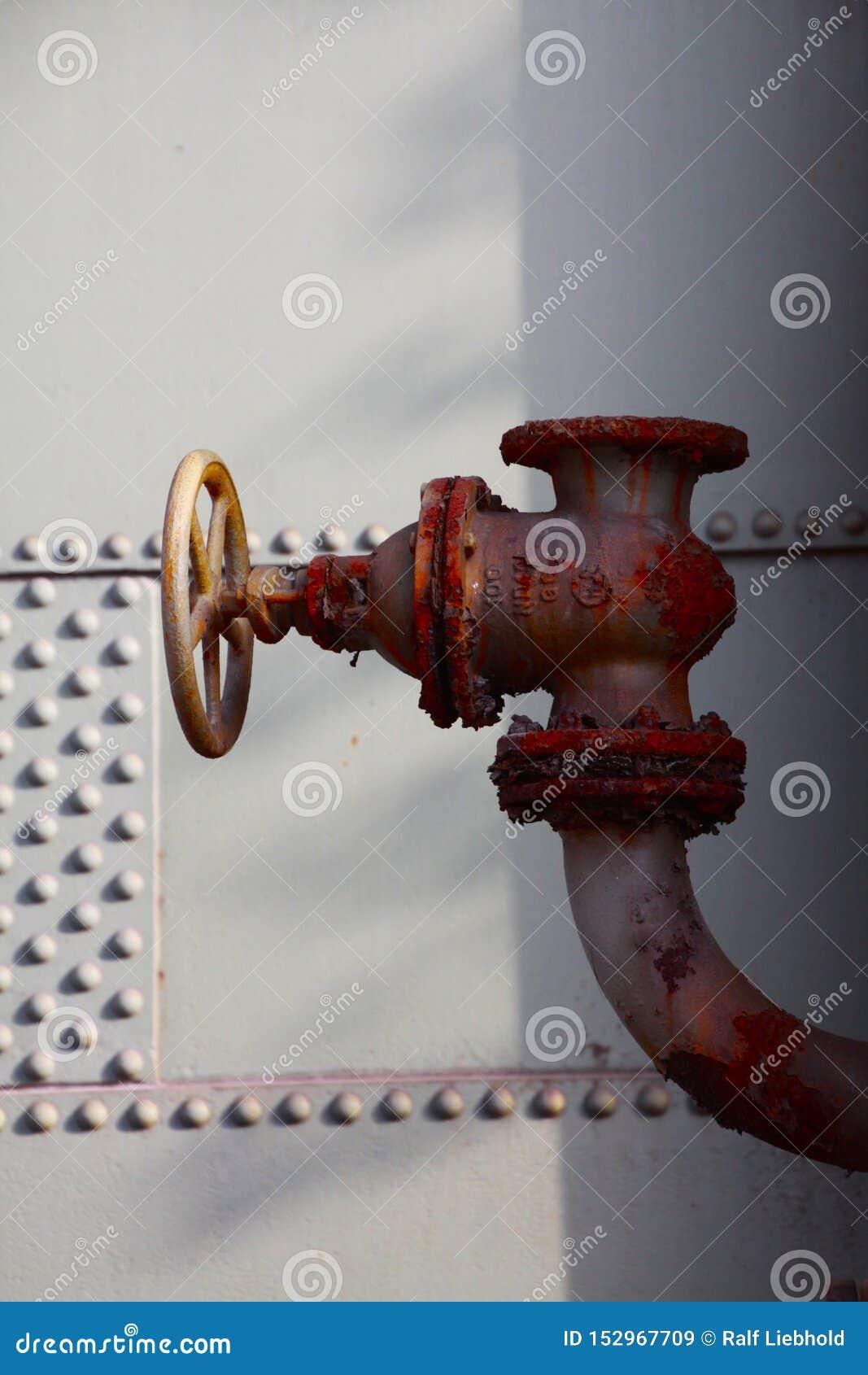 Landschaftspark Duisburgo, Alemania: Ciérrese para arriba de la válvula de control oxidada roja aislada del alivio con las escama