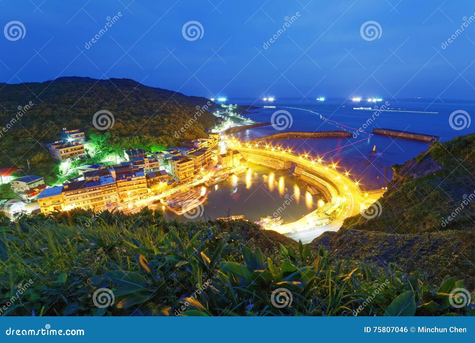 Landschap die van kustweg de haven van een visserijdorp kruisen met lichten van vissersboten op het overzees