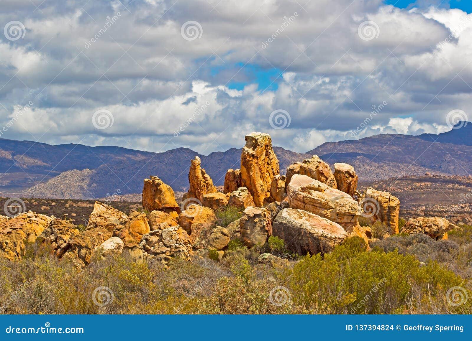 Landschap van roodachtige rotsen, bergen, en hemel
