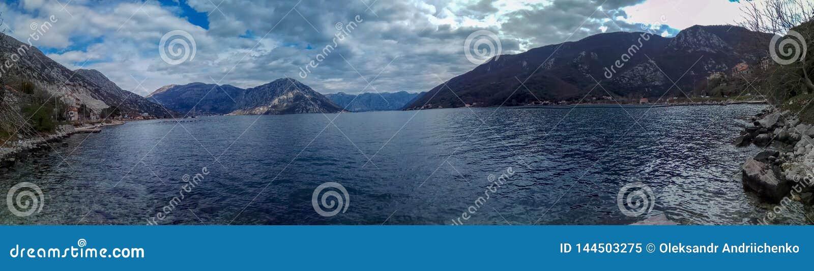 Landschap in verschillende schaduwen van blauw: bergen en hun bezinningen in het kalme water van het Adriatische Overzees